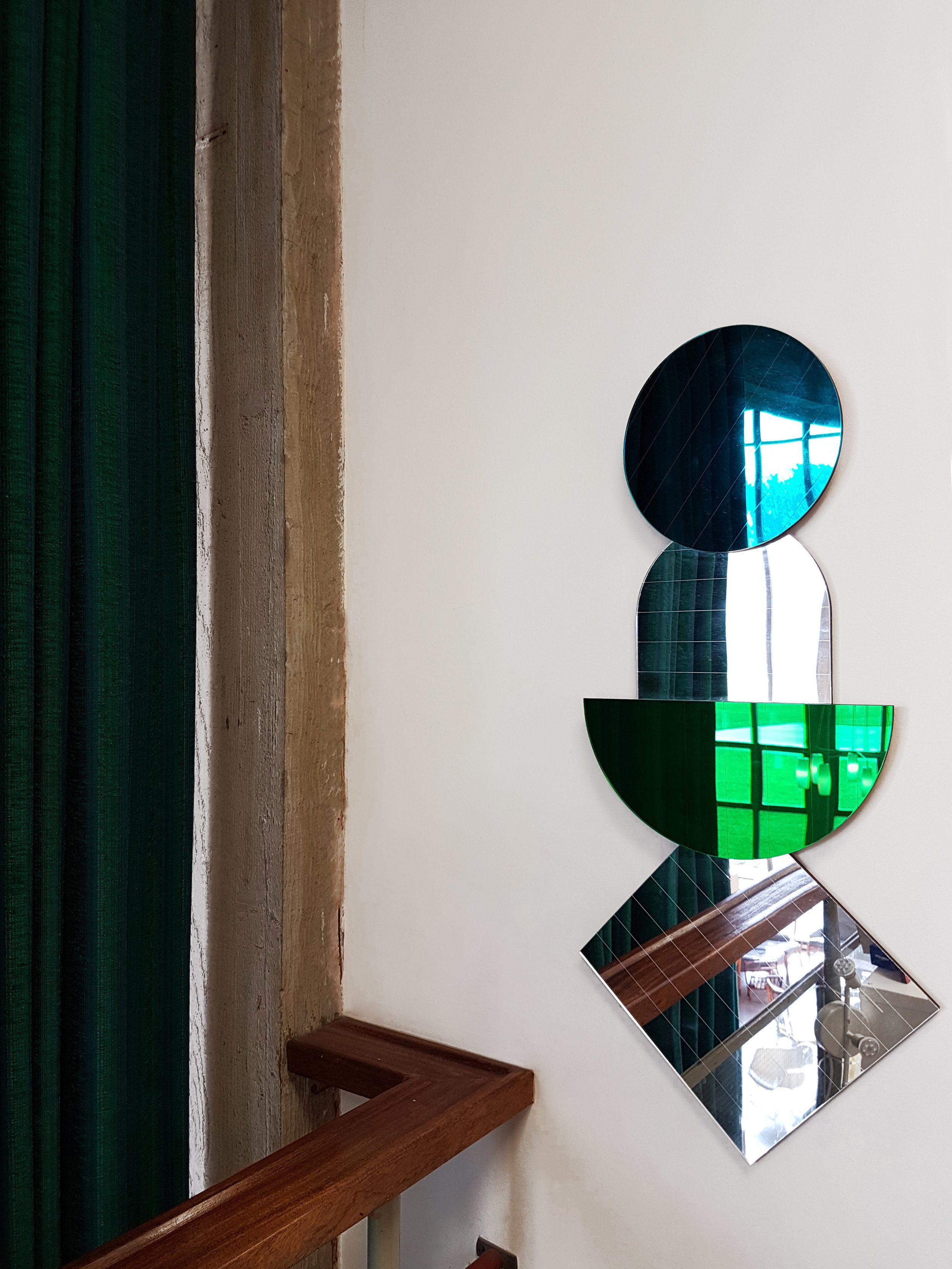 LAYER MIRRORS IN TEAL & EMERALD GREEN - Layer Mirrors looking particuarly oppulent next to the long emerald green curtains and concrete detailing. The four separate mirrors have been hung over each other to create a stacking display.
