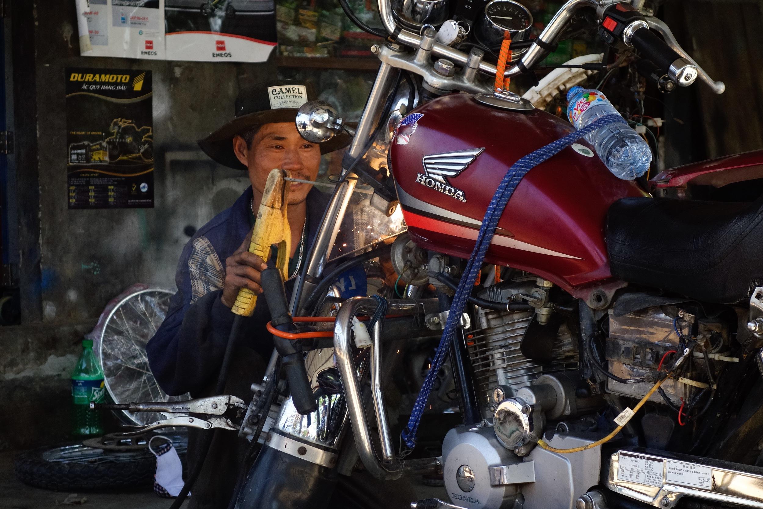A Vietnamese mechanic welding the headlight on a Motorcycle