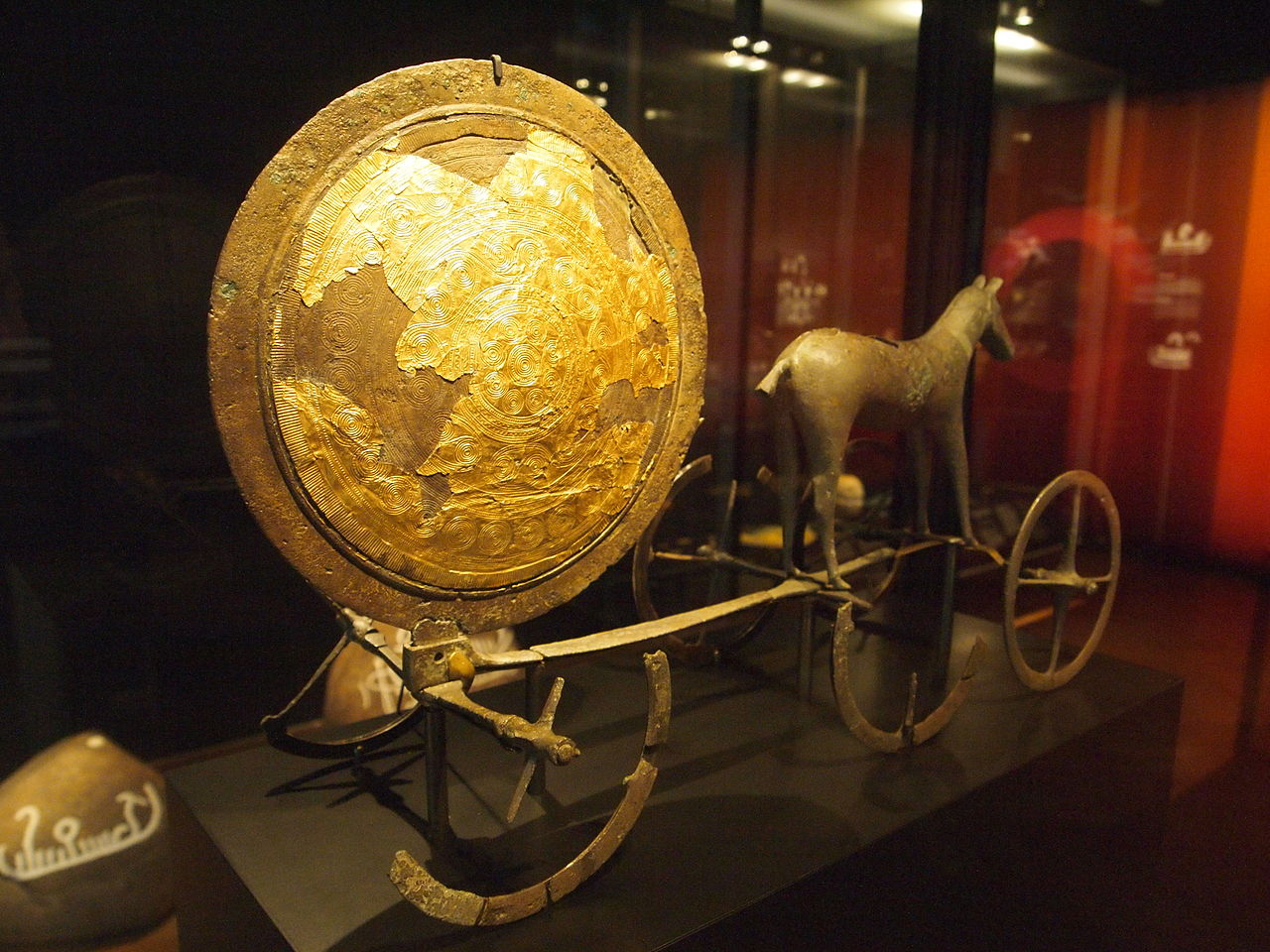 A photograph of the National Museum of Denmark's Bronze Age display, featuring the Trundholm Sun Chariot and various other Nordic Bronze Age items ( Photo:   Wikimedia Commons )