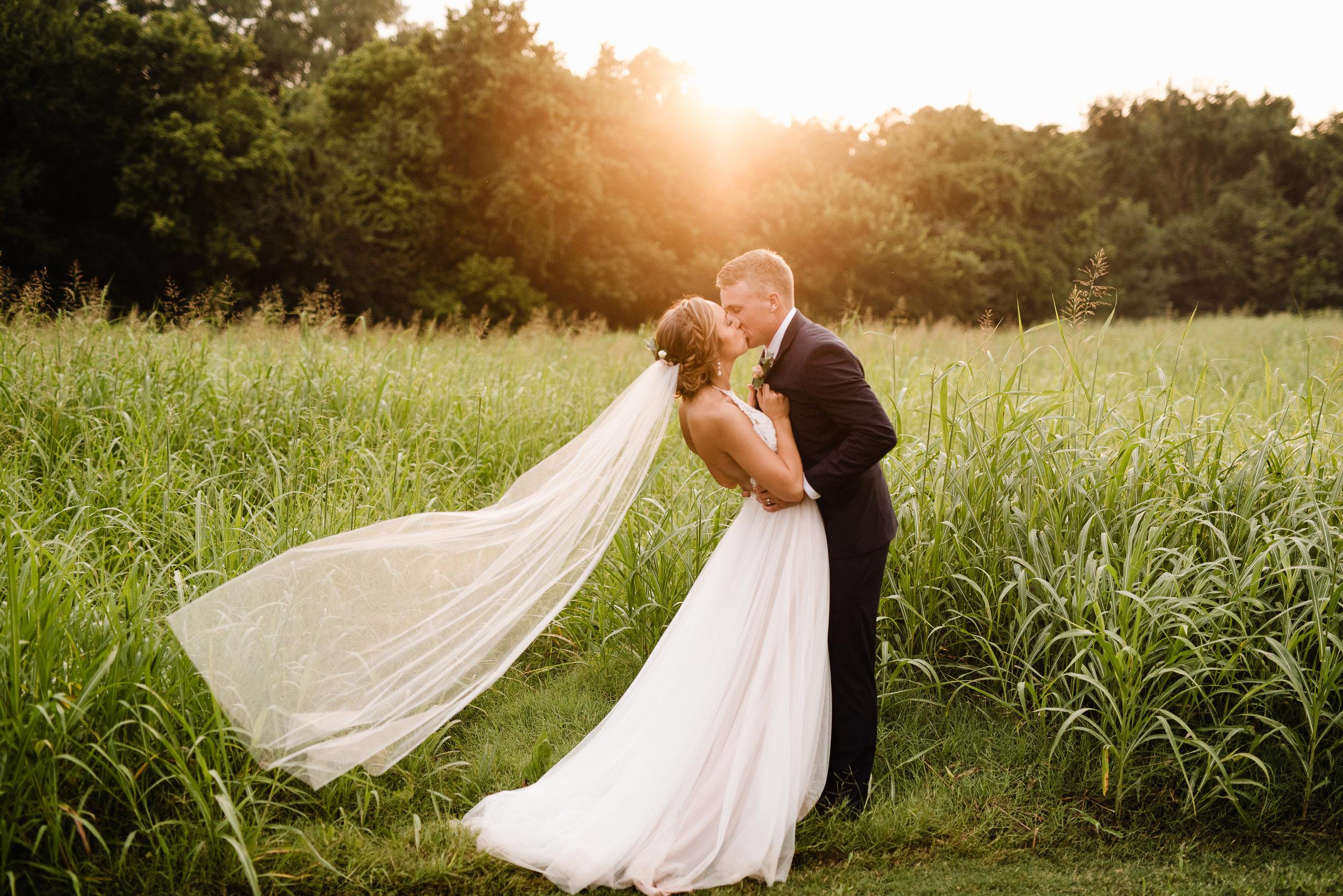 oklahoma wedding photographer bride groom wedding day outside the springs edmond sunset veil wedding day field