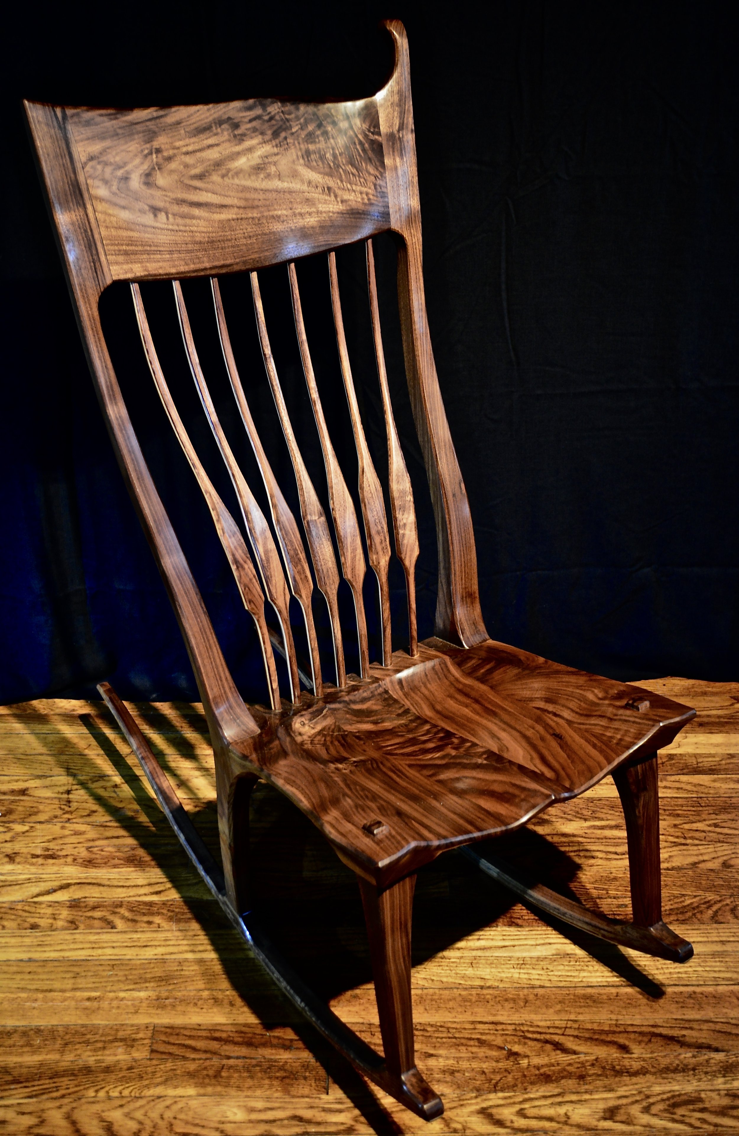 "Armless, ""mother's"" rocker in black walnut."