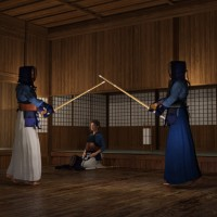 Two Kendo (sword-fighting) combatants in a dojo (training hall). Not sure what role the person in the background is playing, but a 'sensei' would be the teacher.