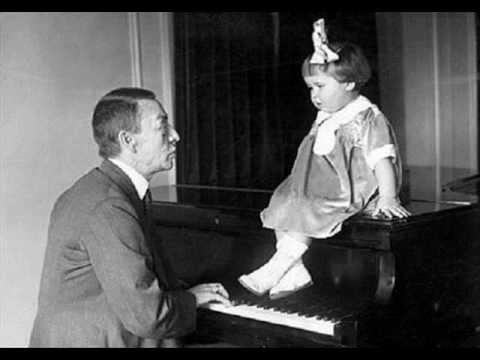 Rachmaninoff on the left (in case there was any doubt) Unknown child perched atop the piano.