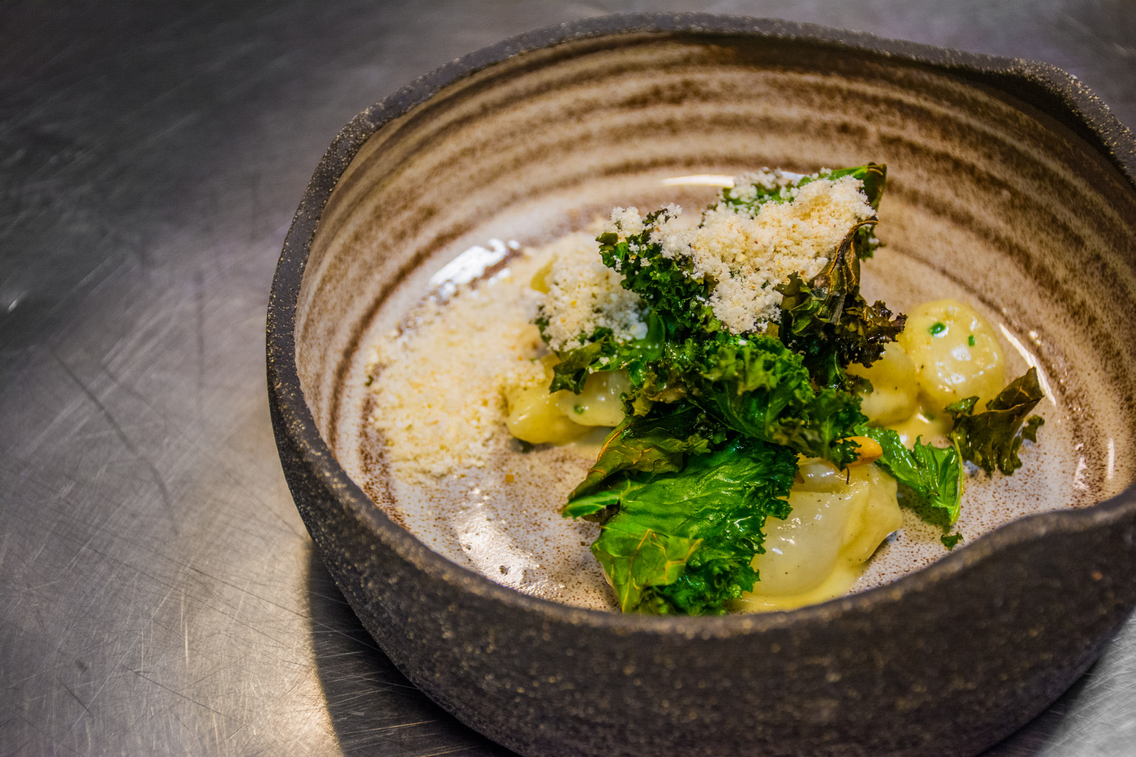 Gnocchi and pecorino served with baked kale, pearl onions, and smoke pine nuts