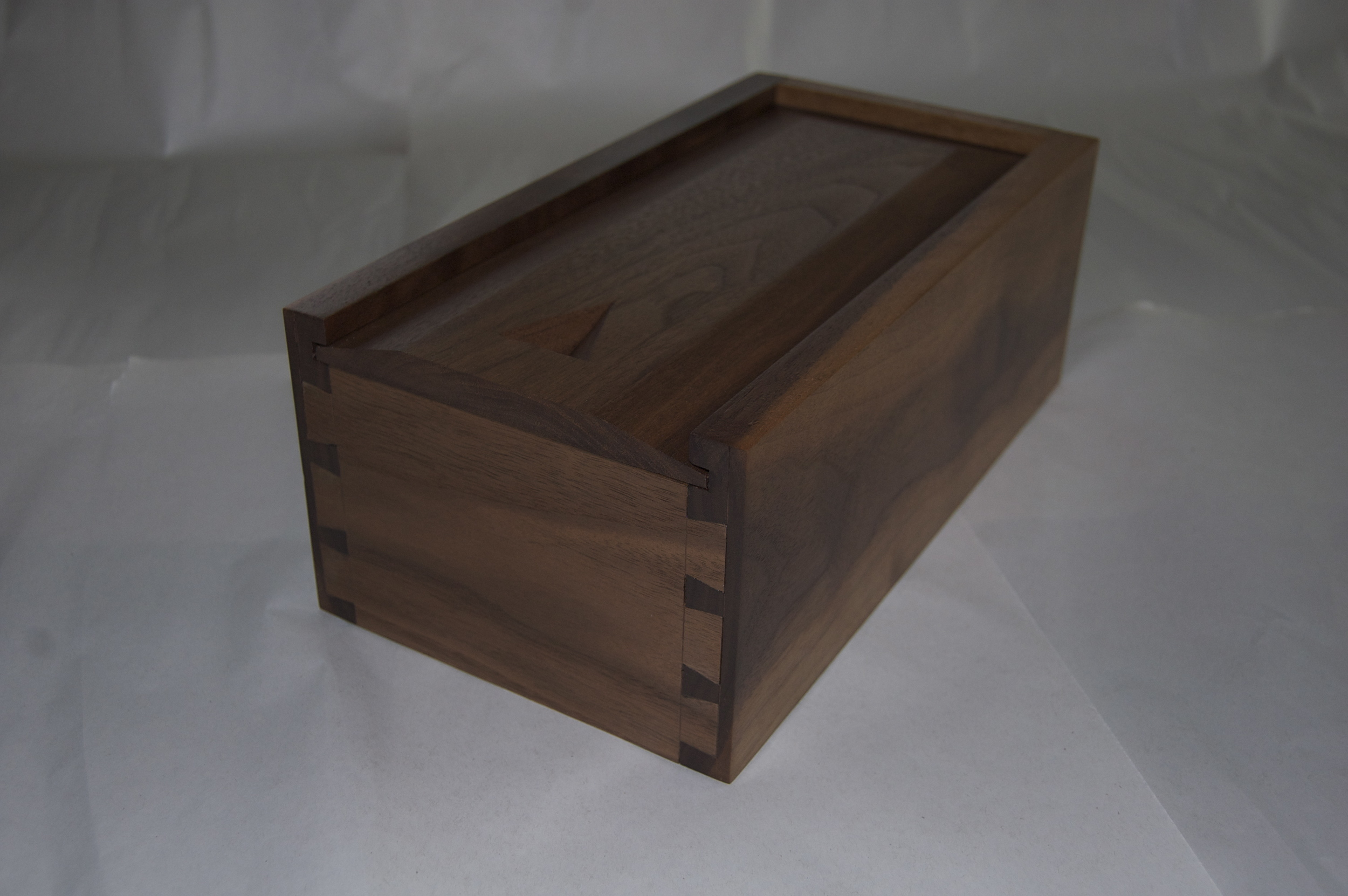 """Material used for this box is walnut. Hand cut dove tails are used to join ends and sides of the box. The raised panel bottom sits in a grove, which allows it to move with changes in the season. The top is also a raised panel on three sides and slides in a grove. The top also has a carved finger pull.A satin oil and urethane finish was applied to show the grain of the wood while providing some protection from everyday use. This box is for sale for $40.00. Dimensions: 12"""" x 6 1/2"""" x 4 1/2"""" (Click on the picture to see how it was put together.)"""