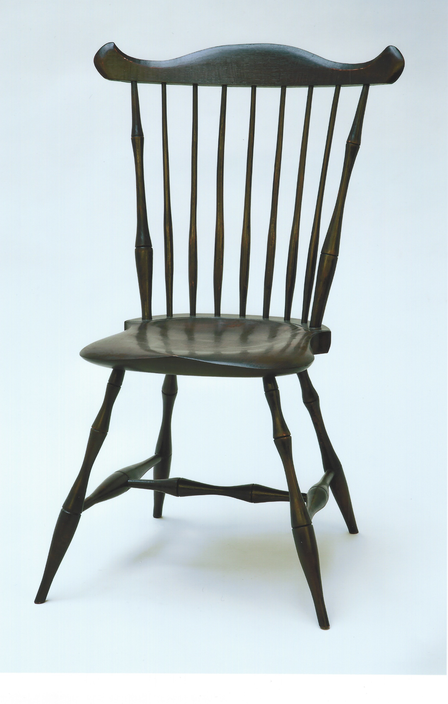 This Windsor Chair has maple legs and stretchers, pine seat and white oak back. The legs, stretchers, and back were made with green wood. Clicking on the chair photo will show that the parts were cut and split from logs and then shaped, turned and steam bent into chair parts. Green wood is used to add strength to the chair. The finish is black over red milk paint and an oil and urethane top coat. The black milk paint is burnished until the red just starts to show through the black. This is done to give the chair a well used appearance. This chair is sold, but we would be glad to build one for you. The price is $1800.00