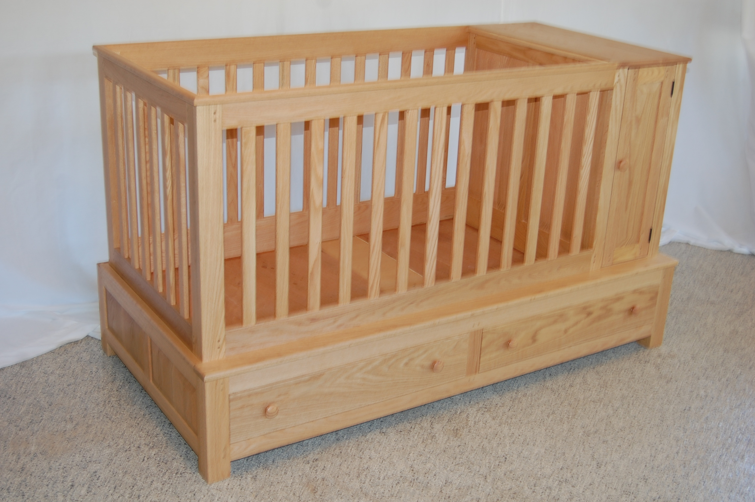 """This crib was made for Abigail,our first granddaughter. It converts into a youth bed once she out grows the crib. Red oak was used to make this piece, except for the drawer bottoms, which are 1/4"""" oak plywood. The platform the mattress rests on is 3/4"""" plywood. There is a cabinet on the right side and two drawers under the crib. The finish is oil and urethane.Dimensions: 661/2""""wide x 40""""high x 35""""deep."""