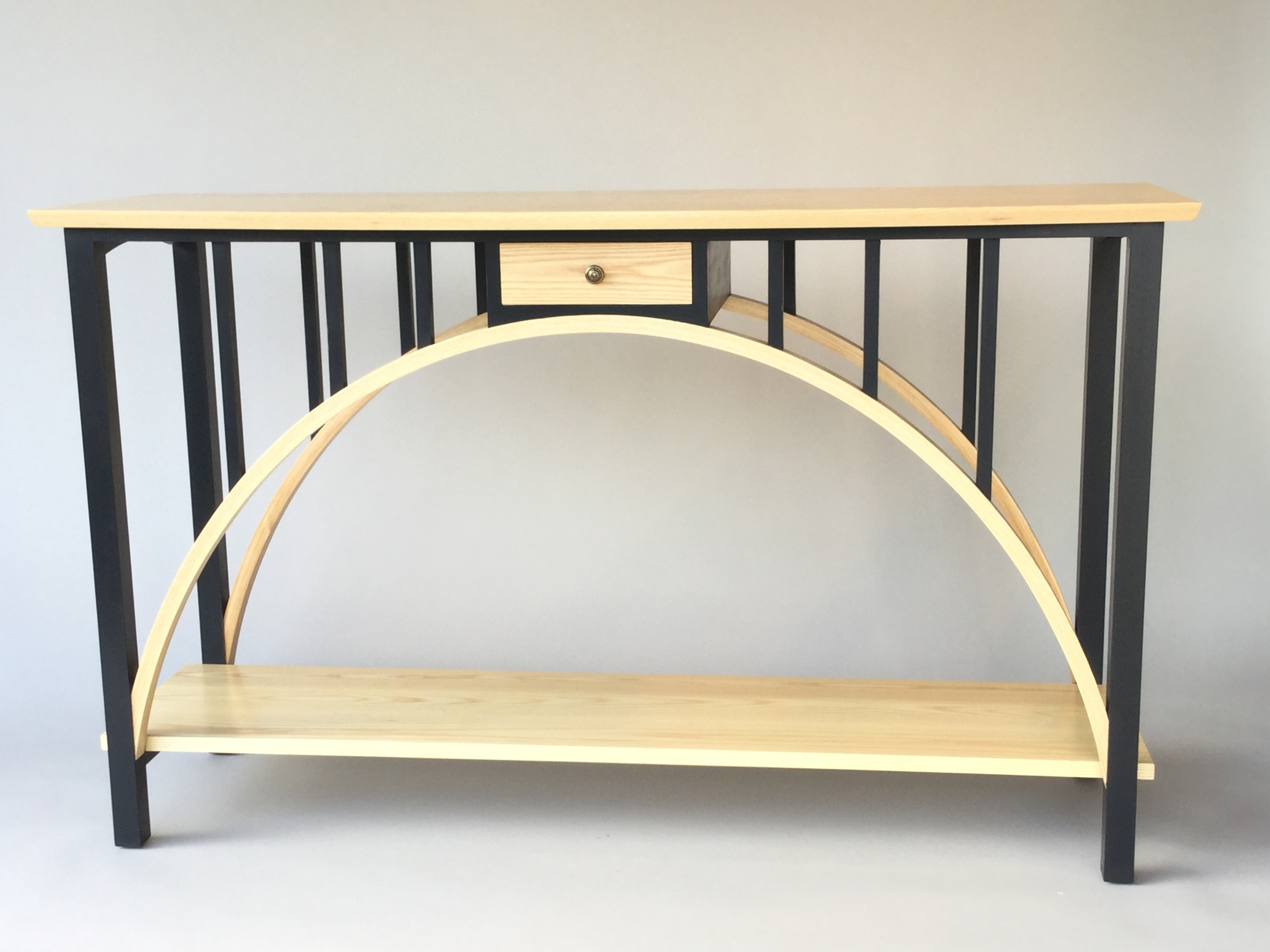 """This hall / sofa table is our own design. The table top, drawer front, arches and bottom shelf are ash, everything else is poplar. Both arches are 5 layer bent lamination. All visible poplar parts are finished with a black milk paint. The entire piece has an oil and urethane top coat. This table is for sale at $3000.00. Dimensions: 35""""H x 60""""W x 20""""D (Click on the picture to see how it was put together.)"""
