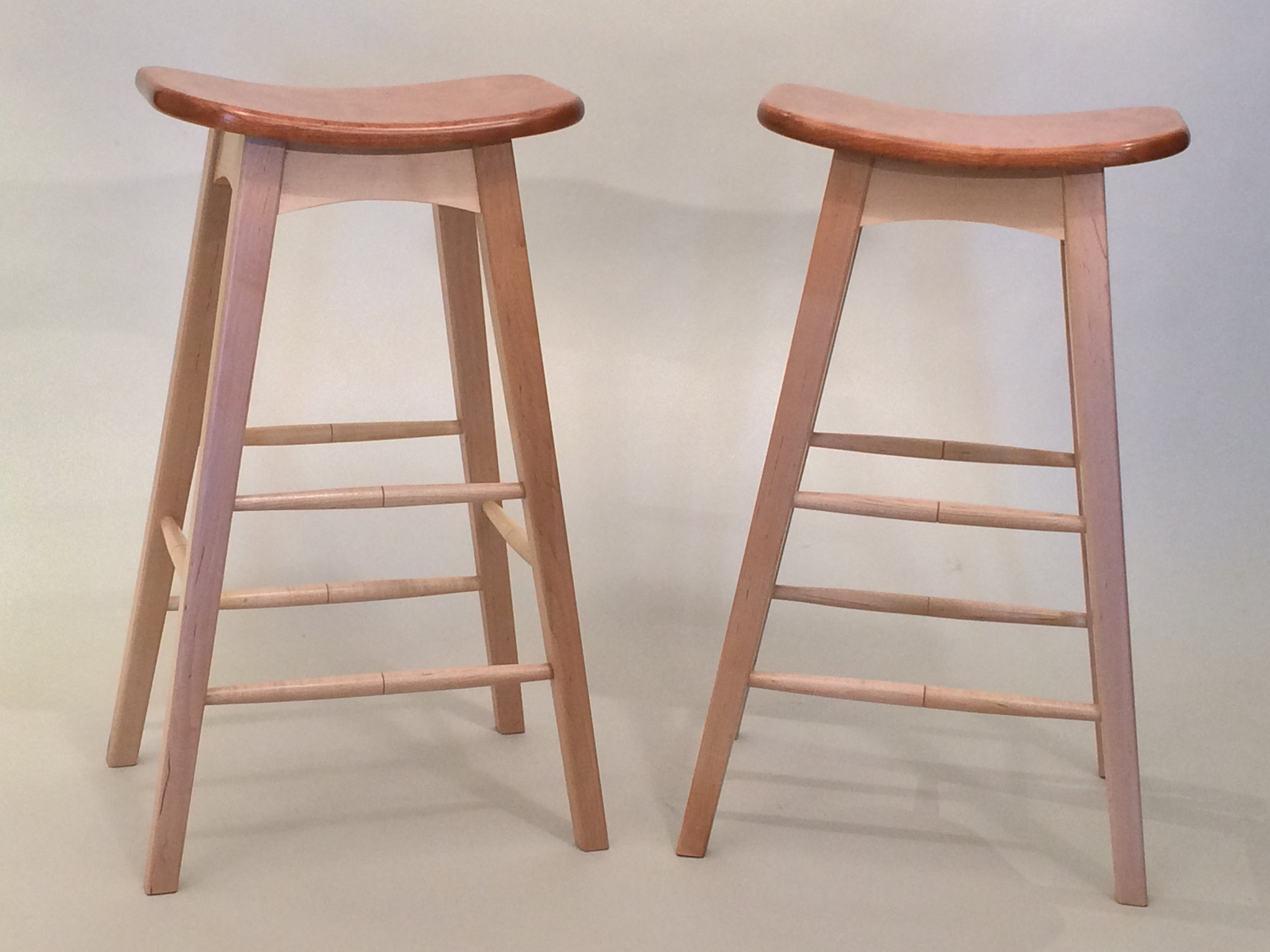 This a pair of bar stools will be used at a sewing bench. Legs, rails and stretchers are maple and the seats are cherry. The seats were shaped out of 2 inch thick pieces of cherry. The finish is an oil and urethane top coat. The stools are 29 inches tall. Price is $450.00 each.