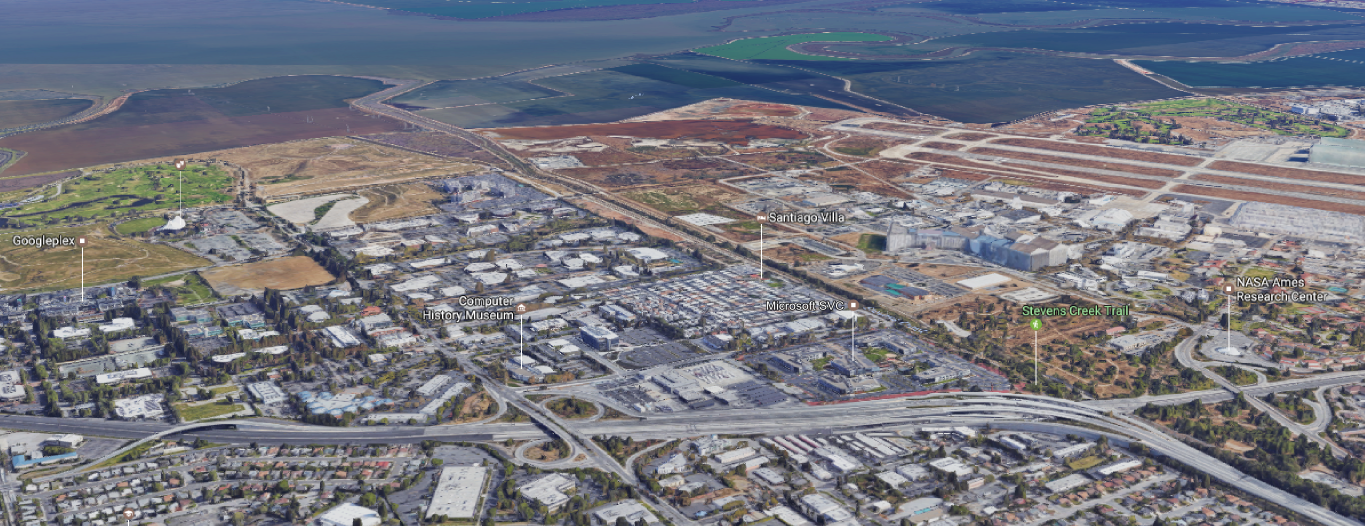 Mountain View, California, looking northeast over US 101 and San Francisco Bay. The Computer History Museum sits between the Googleplex and NASA Ames. Hangar 1, the giant airship hangar, is visible on the right of the image. Imagery and map data © Google, Landsat/Copernicus.