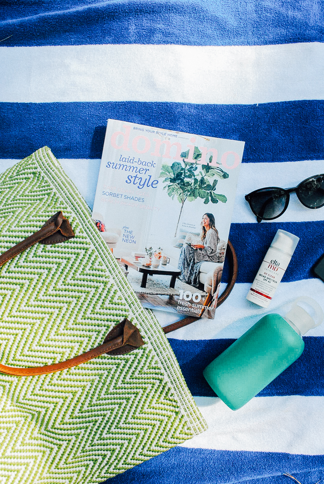 Inside my Beach Bag: Domino Magazine, Elta MD Sunscreen, Oliver Peoples Sunglasses, BKR Water Bottle, Annie Selke Tote.