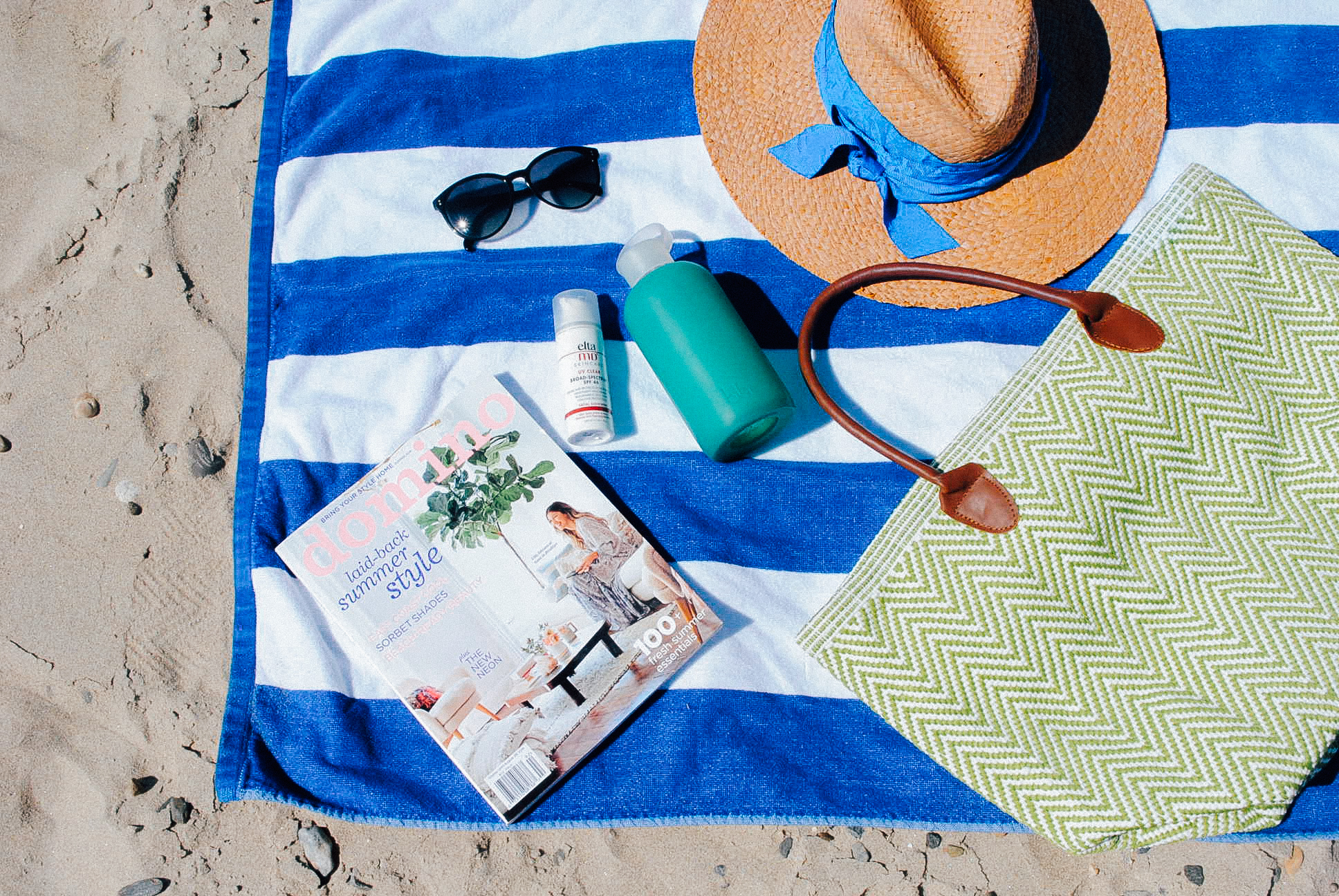 Dash & Albert Beach Bag (gifted)  Striped Beach Towel.   Sunglasses.    BKR Water Bottle.     Sunscreen.     Domino Magazine.    Lola Hat.