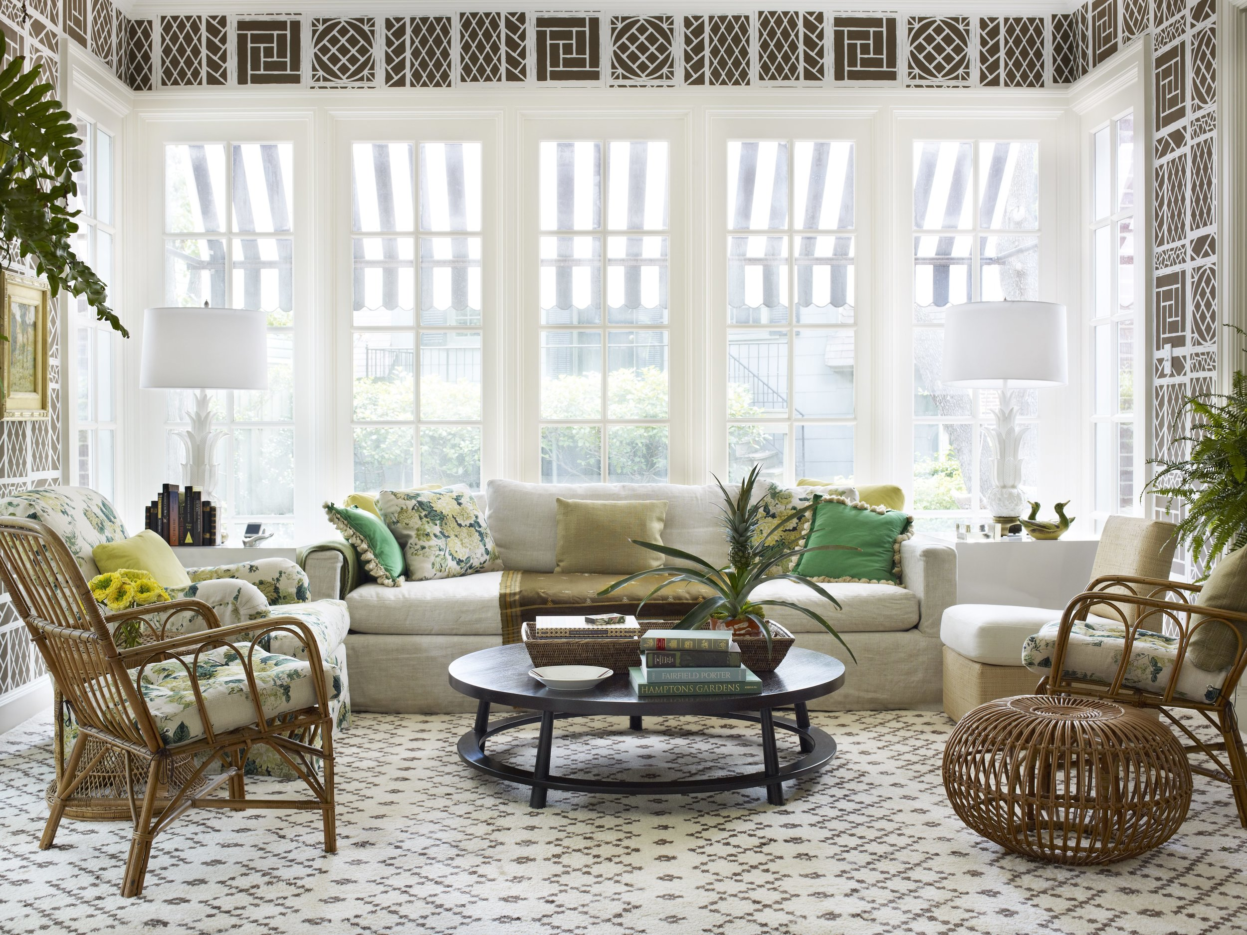 A sunroom in the Highland Park neighborhood of Dallas. With China Seas Lyford Trellis wallpaper and Clarence House's Dahila print on the pillows and chairs.