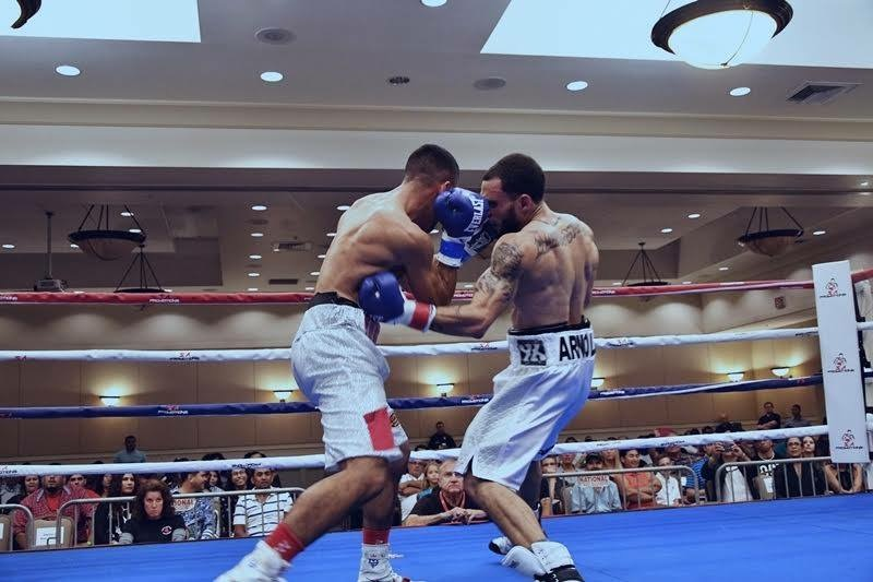 Dustin Arnold lands a left hook to the body on Evander Lamourt in his professional debut. Photo: Alex Nunez/PR   Boxea