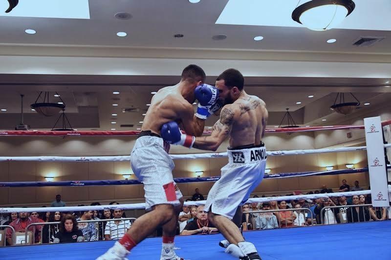 Dustin Arnold lands a left hook to the body on Evander Lamourt in his professional debut. Photo: Alex Nunez/PR   Boxea