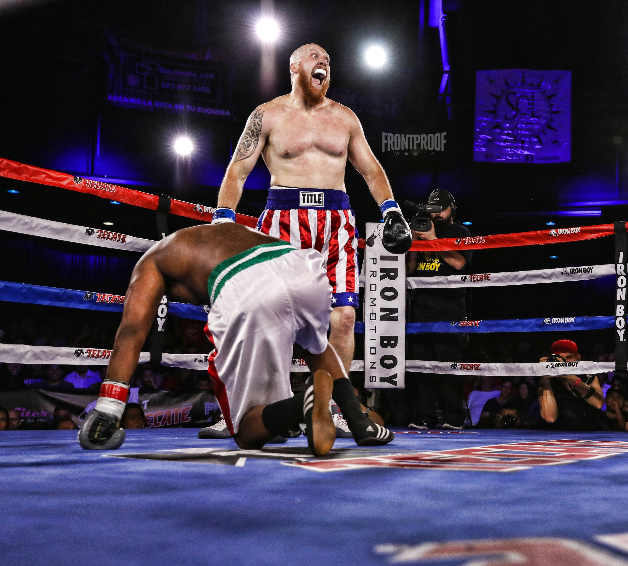 Adam Stewart (red, white & blue shorts) stands over his opponent, Michael Smith, after a first round knockdown that gave him the victory. Photo: Kelly Owen/Frontproof Media.