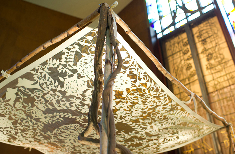 this chuppah frame is made out of branches; the canopy is a piece of cloth tied to them.