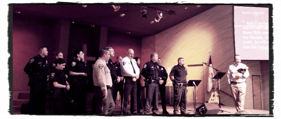 Pastor Michael Guzman reading Romans 13 over the Exeter Police Officers