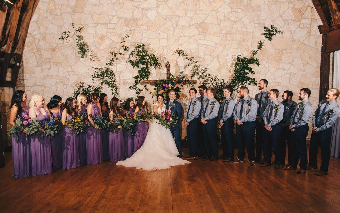 With such a large wedding party, the coordination of bouquets and boutonnieres is a bit more complicated. Each member's personal flowers were reflected directly in the bride's bouquet, creating a visual connection.  Photo credit:  Kat/Eye Studios