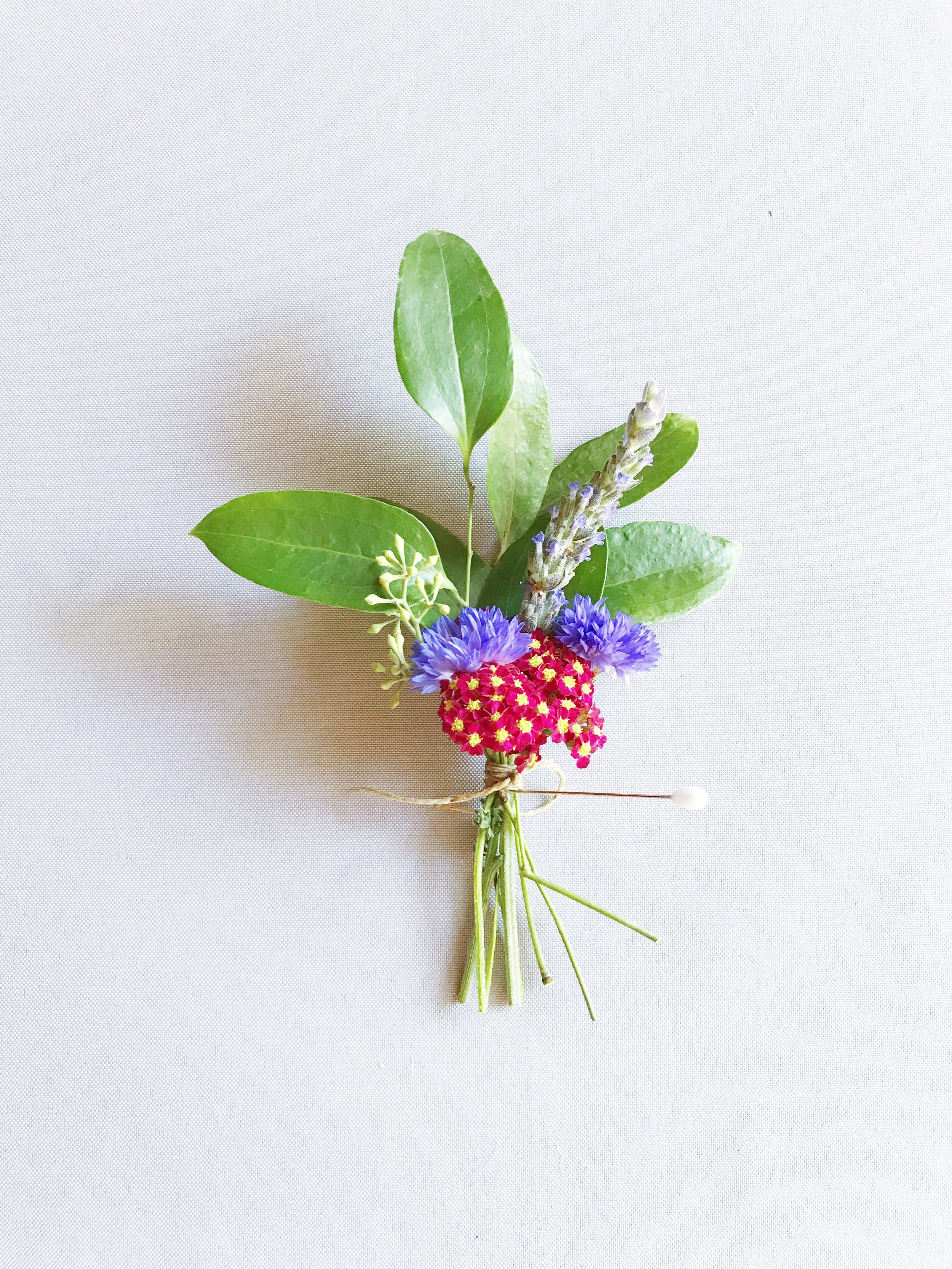 Smilax, seeded eucalyptus, red cottage yarrow, cornflower, and lavender composed some of the family's boutonnieres.