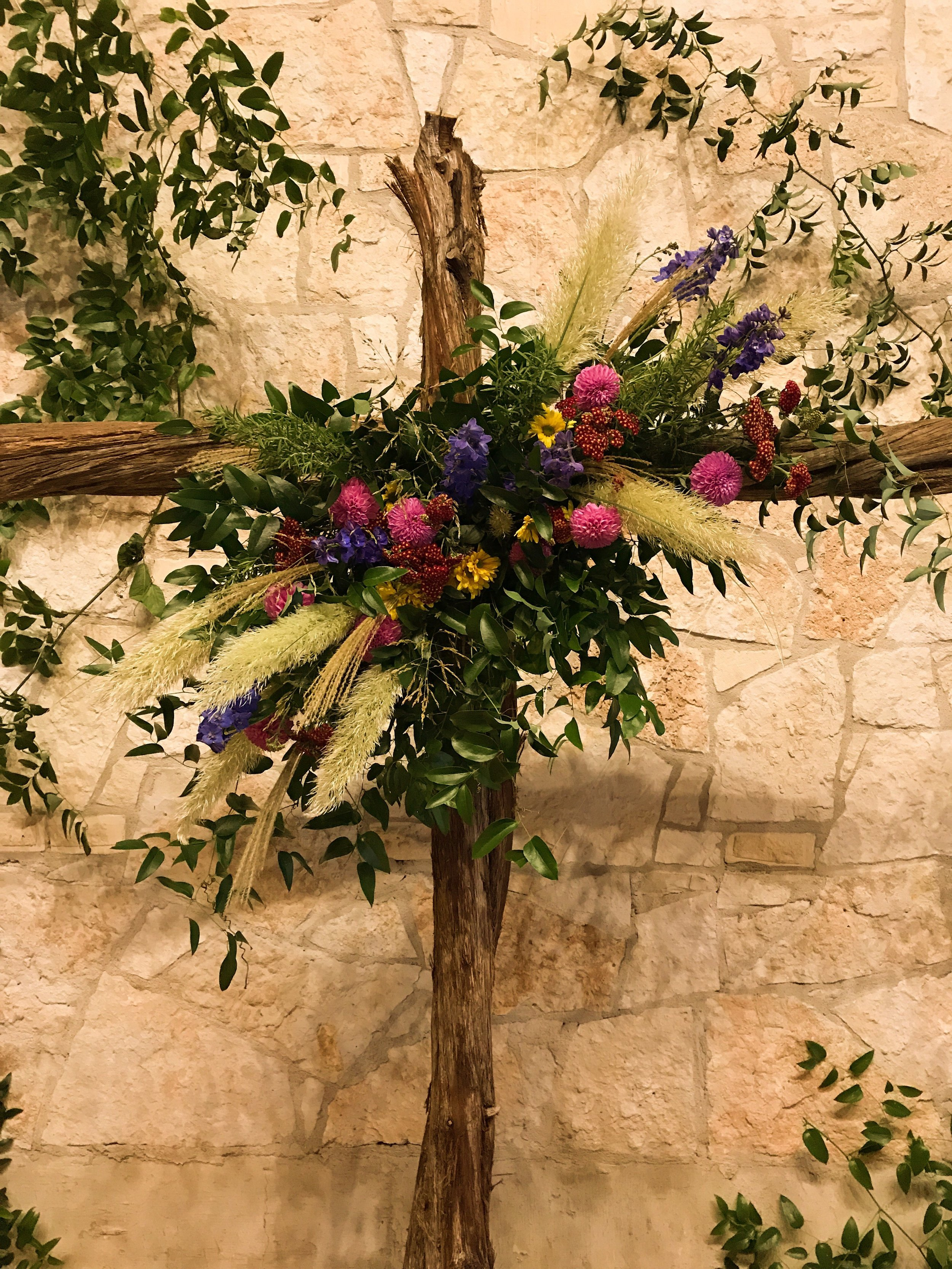 This cross made from cedar stood about 9 feet tall and served as the centerpiece of the ceremony's backdrop. The couple wanted it to be adorned with flowers and greenery, much like the bouquets and boutonnieres, but also wanted to be able to reuse it for the sweetheart table at the reception.