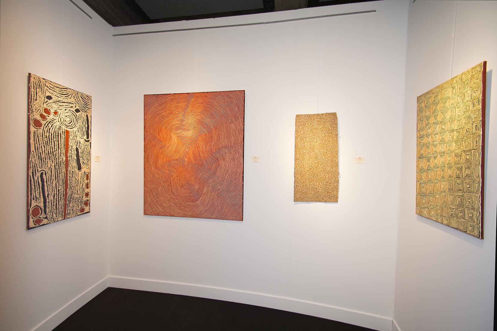 De gauche à droite différentes peintures Aborigènes du centre d'art de Papunya Tula : L'artiste Ningura Napurrula, une œuvre importante de l'artiste Warlimpirrnga Tjapaltjarri un des derniers nomades, l'artiste Gulumbu Yunupingu du centre d'art de Yirrkala, une toile en noir et blanc de l'artiste Ray James Tjangala de Papunya.