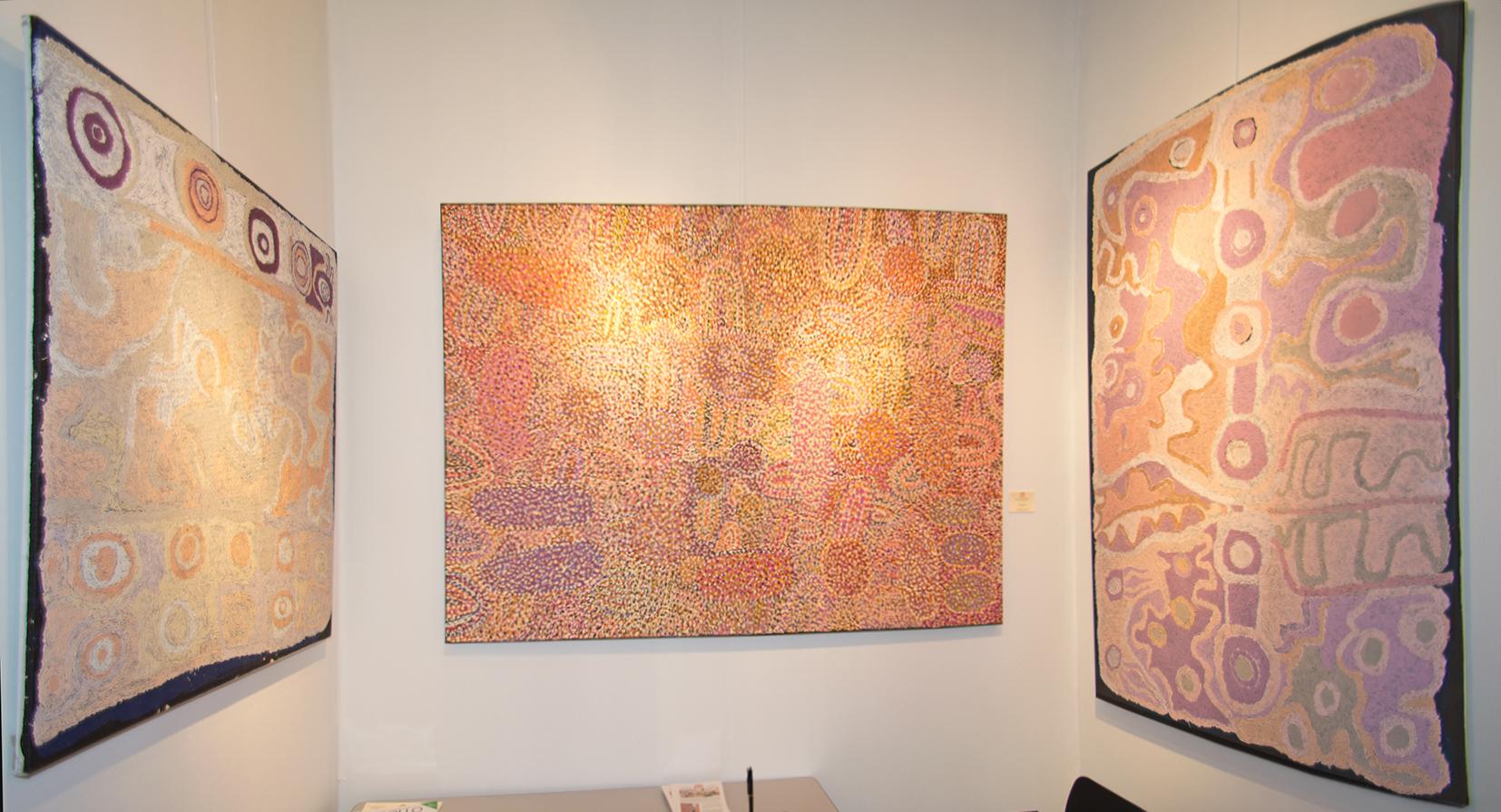 A droite et à gauche, se faisant face, l'artiste Aborigène d'Australie, Angkaliya Curtis dans deux œuvres aux tons pastels autour de la mythologie du rêve des sept sœurs. Au centre une toile de l'artiste Ngupulya Pumani Margaret du centre d'art de Mimili Maku où les signes évoqués s'évanouissent derrière un pointillisme de circonstance pour atténuer la portée d'éléments sensibles.