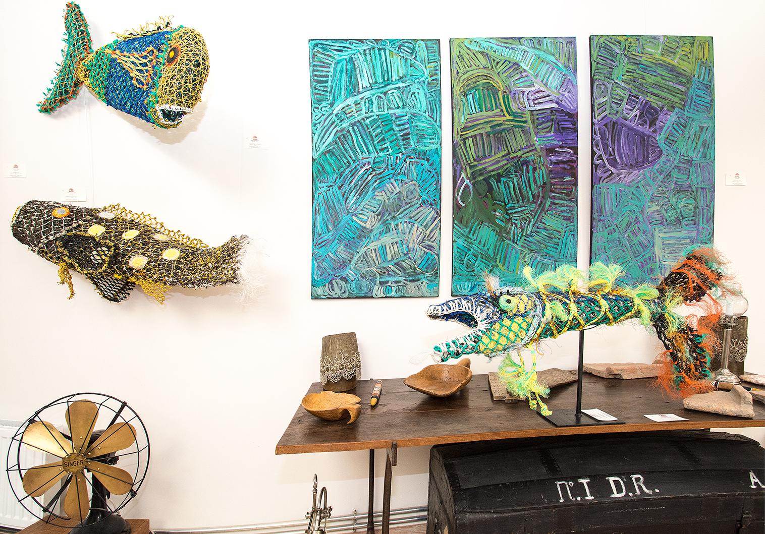"""Vue de l'exposition d'art Aborigène """"Entre Deux Eaux"""". De gauche à droite. Sculptures en filets de pêche recyclés des artistes Aborigènes du Erub art centre : les artistes Rachel Emma Gela et en dessous Florence Gutchen. Sur le mur un triptyque de l'artiste Sonia Kurarra du centre d'art de Mangkaja. Sur la table une sculpture en d'Erub de l'artiste Ellarose Savage. © Photo : Aboriginal Signature, with the courtesy of the artists and the art centres."""
