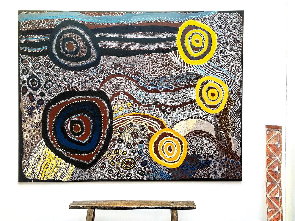 """Vue de l'exposition d'art Aborigène """"Empreintes Eternelles"""" en partenariat avec Tjungu Palya Arts. Toile collaborative Watarru. Titre : Ilpili. Format : 200 x 150 cm. A la droite de la peinture : un pôle de cérémonie en tronc d'eucalyptus peint en pigments naurels, de la communauté Aborigène de Maningrida."""