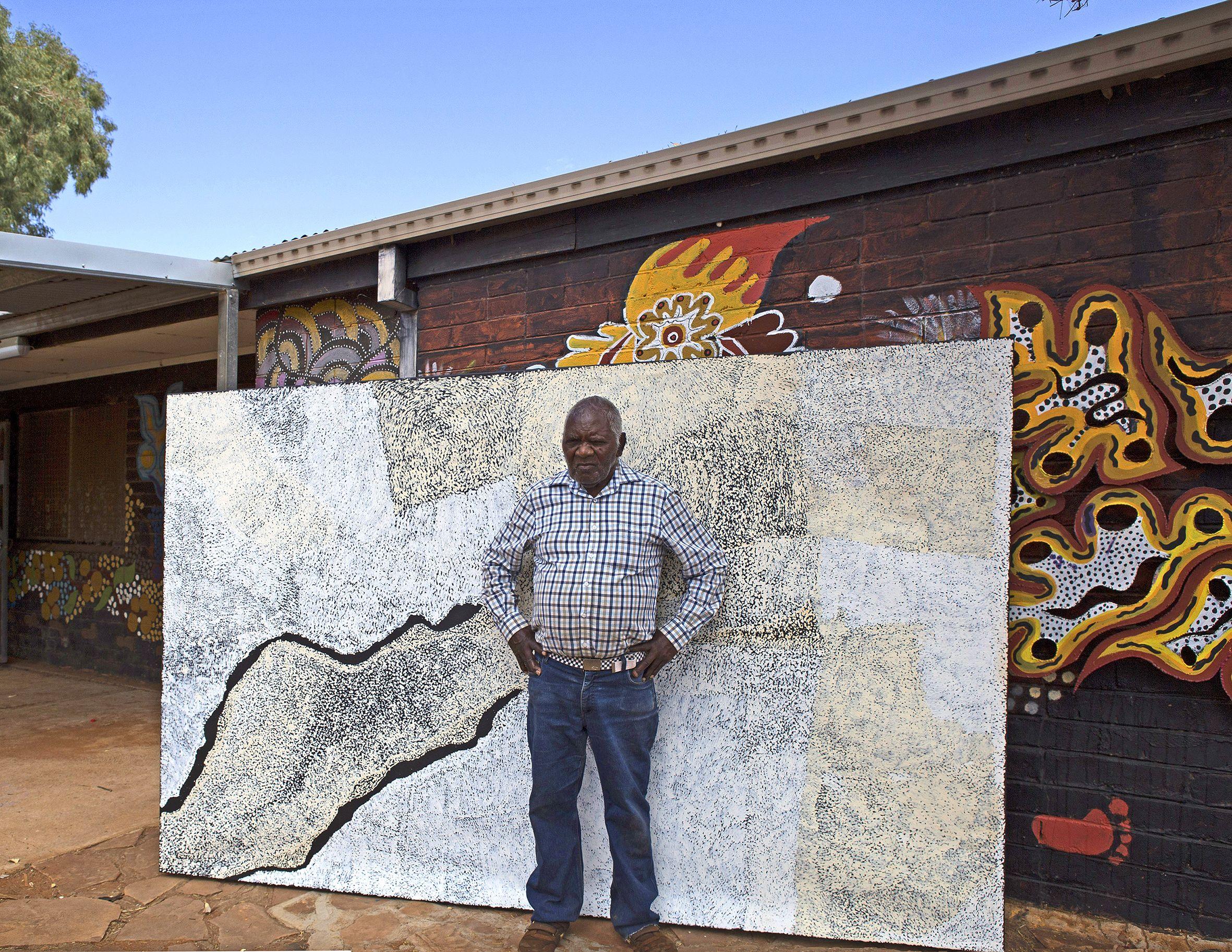 Pepai Jangala Carroll posant avec son œuvre magistrale, juste devant le mur du centre d'art d'Ernabella dans le APY land. © Photo Ernabella Arts with the courtesy of the artist.