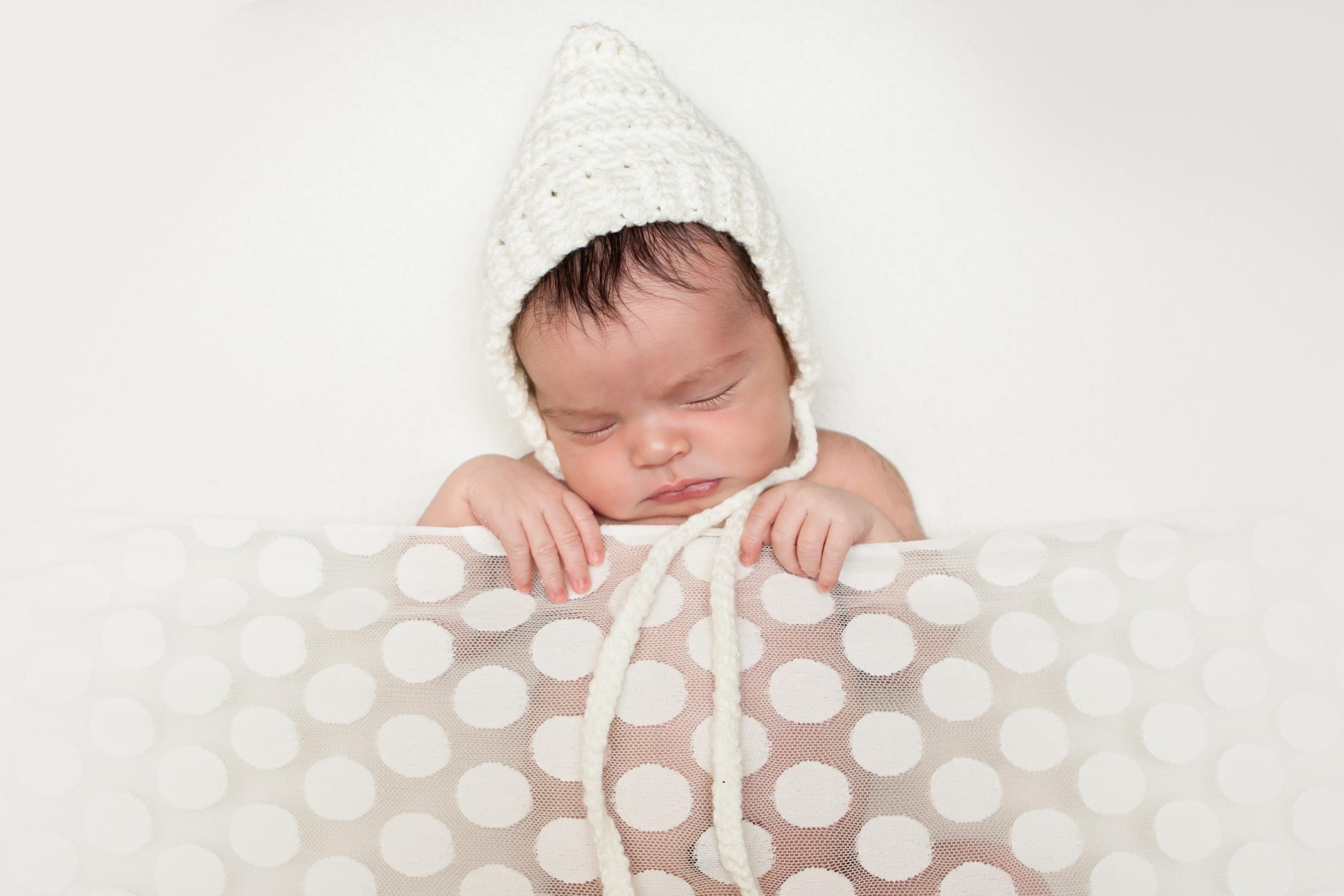Newborn baby girl white blanket tucked in creme bonnet, Westchester County, NY Newborn Photographer Amanda Noelle Photography.