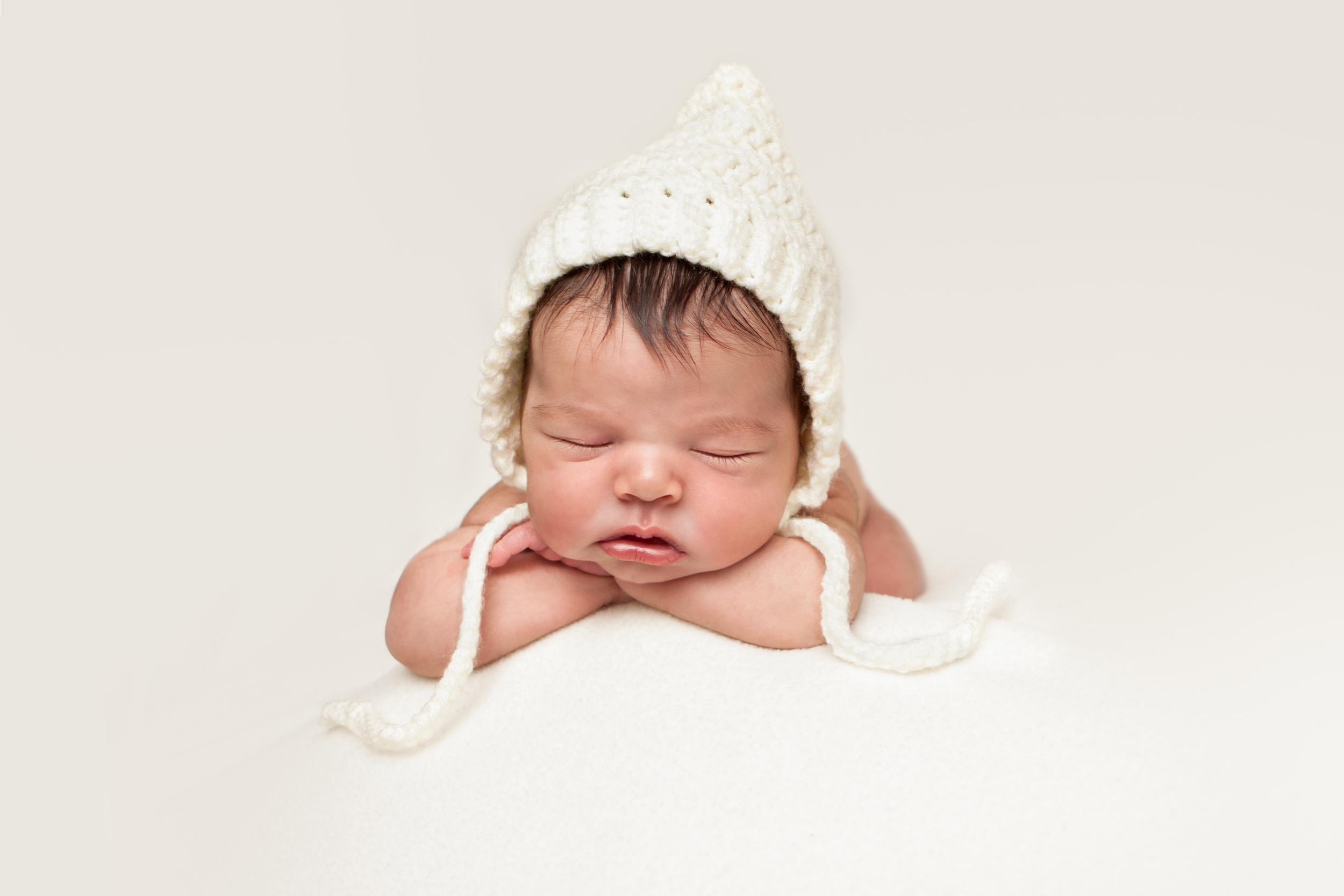Newborn baby girl white blanket creme bonnet chin on wrists, Westchester County, NY Newborn Photographer Amanda Noelle Photography.