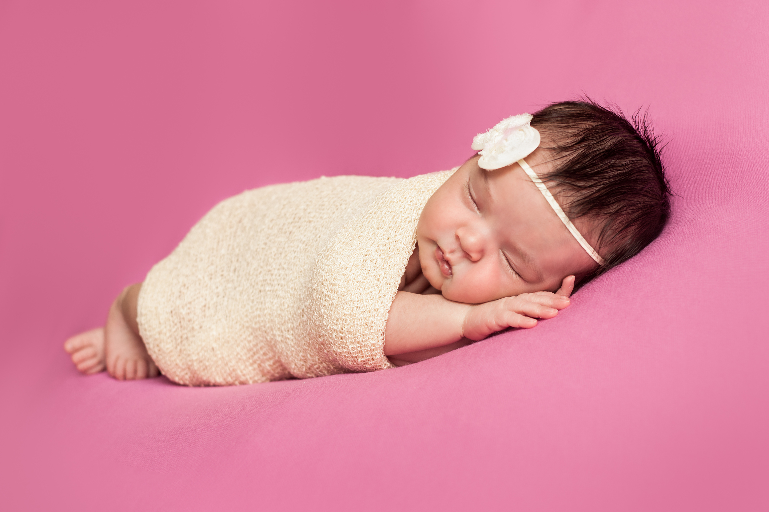 Newborn baby girl wrapped in creme stretch wrap with creme bow headband on pink background, Westchester County, NY Newborn Photographer Amanda Noelle Photography.