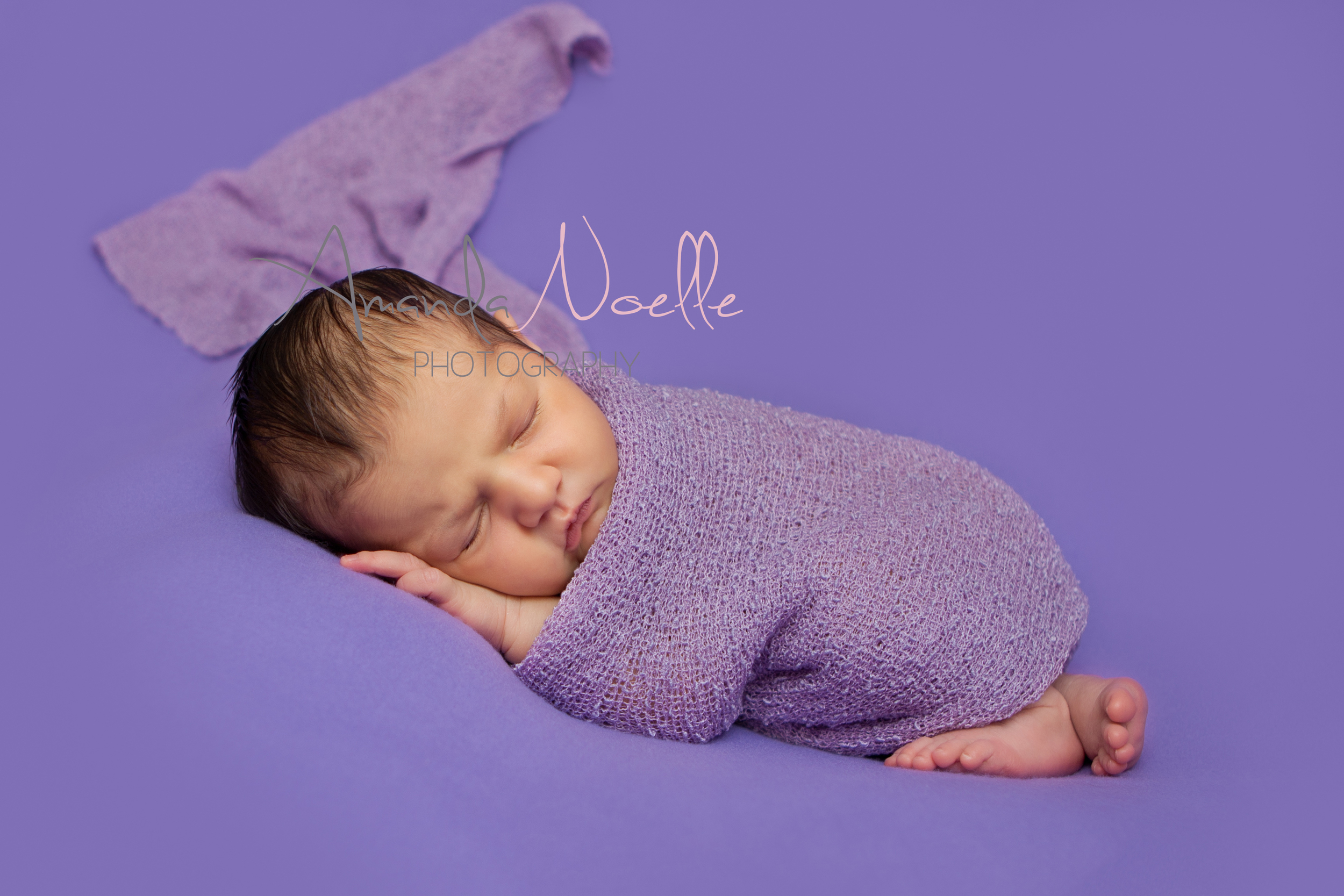 Newborn baby girl, purple background fabric, purple stretch wrap draped, sleeping pose on beanbag, by Westchester, New York Newborn Photographer, Amanda Noelle Photography
