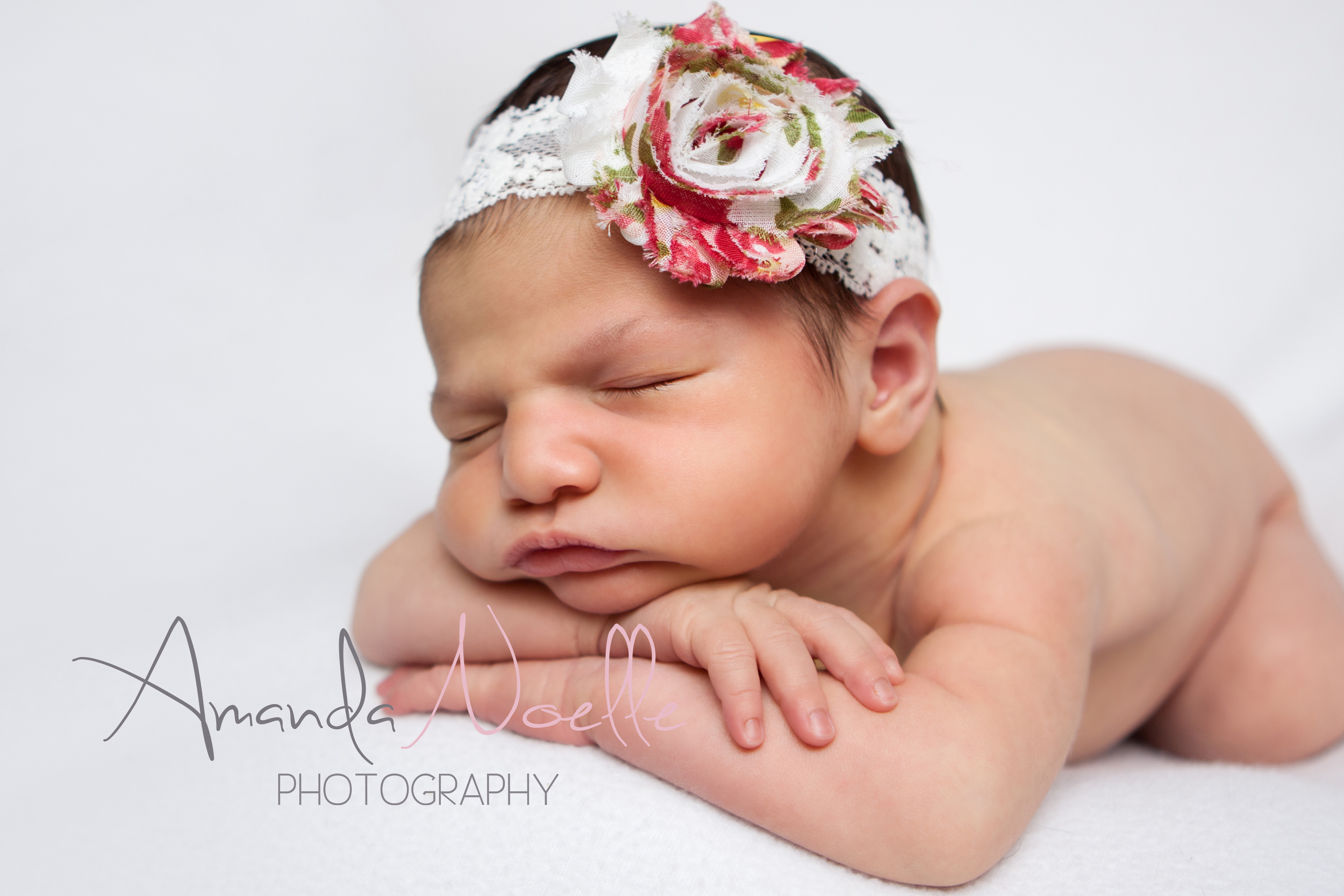 Newborn baby girl, white background fabric, white lace pink shabby chic flower headband, sleeping pose chin on hands on beanbag, by Westchester, New York Newborn Photographer, Amanda Noelle Photography