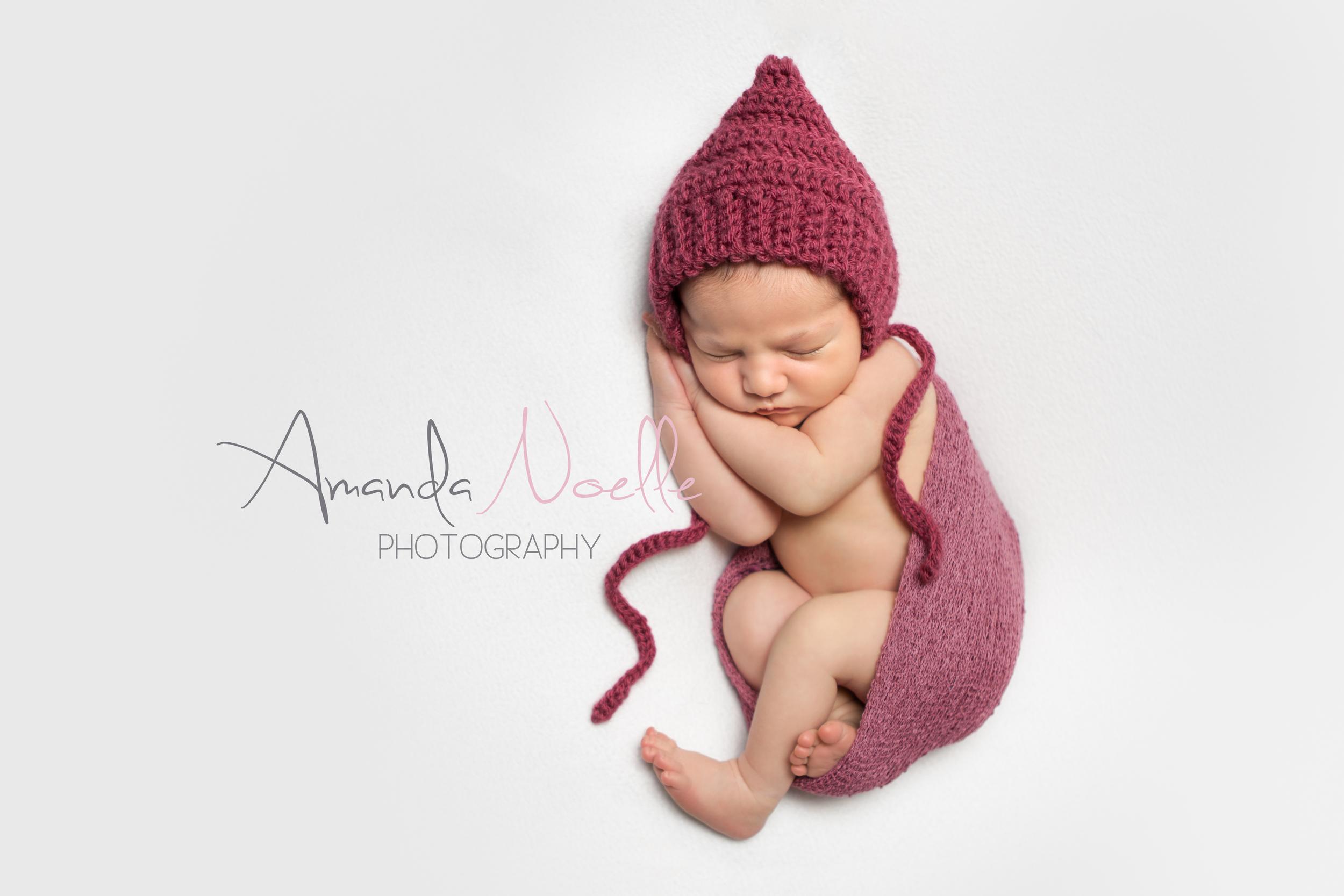 Newborn baby girl, white background fabric, dark pink maroon crochet bonnet, stretch wrap, sleeping pose on beanbag, by Westchester, New York Newborn Photographer, Amanda Noelle Photography