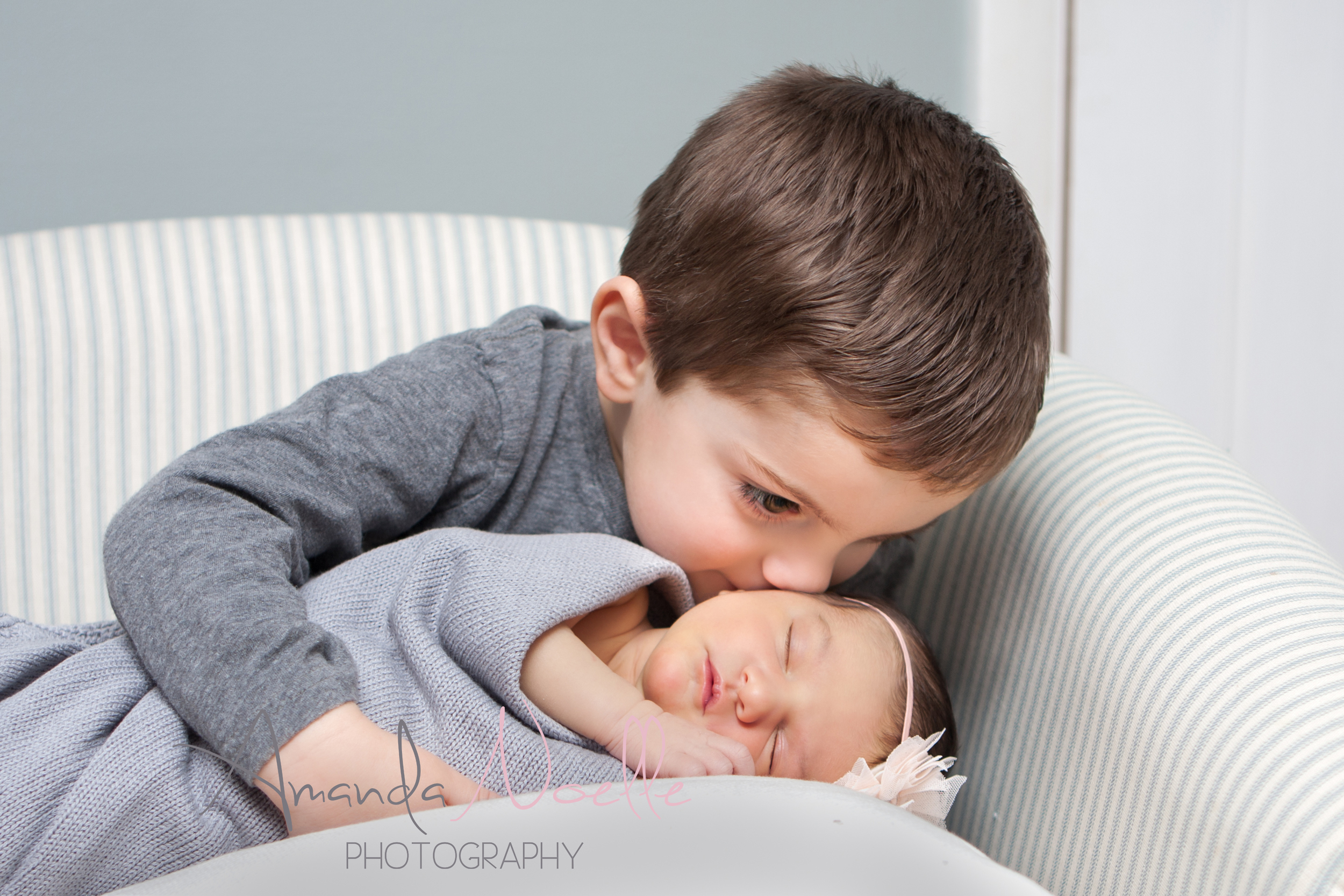 Newborn baby girl, big brother toddler kissing little baby sister, sibling photography, sitting in chair, newborn on pillow, grey color scheme with pink headband by Westchester, New York Newborn Photographer, Amanda Noelle Photography