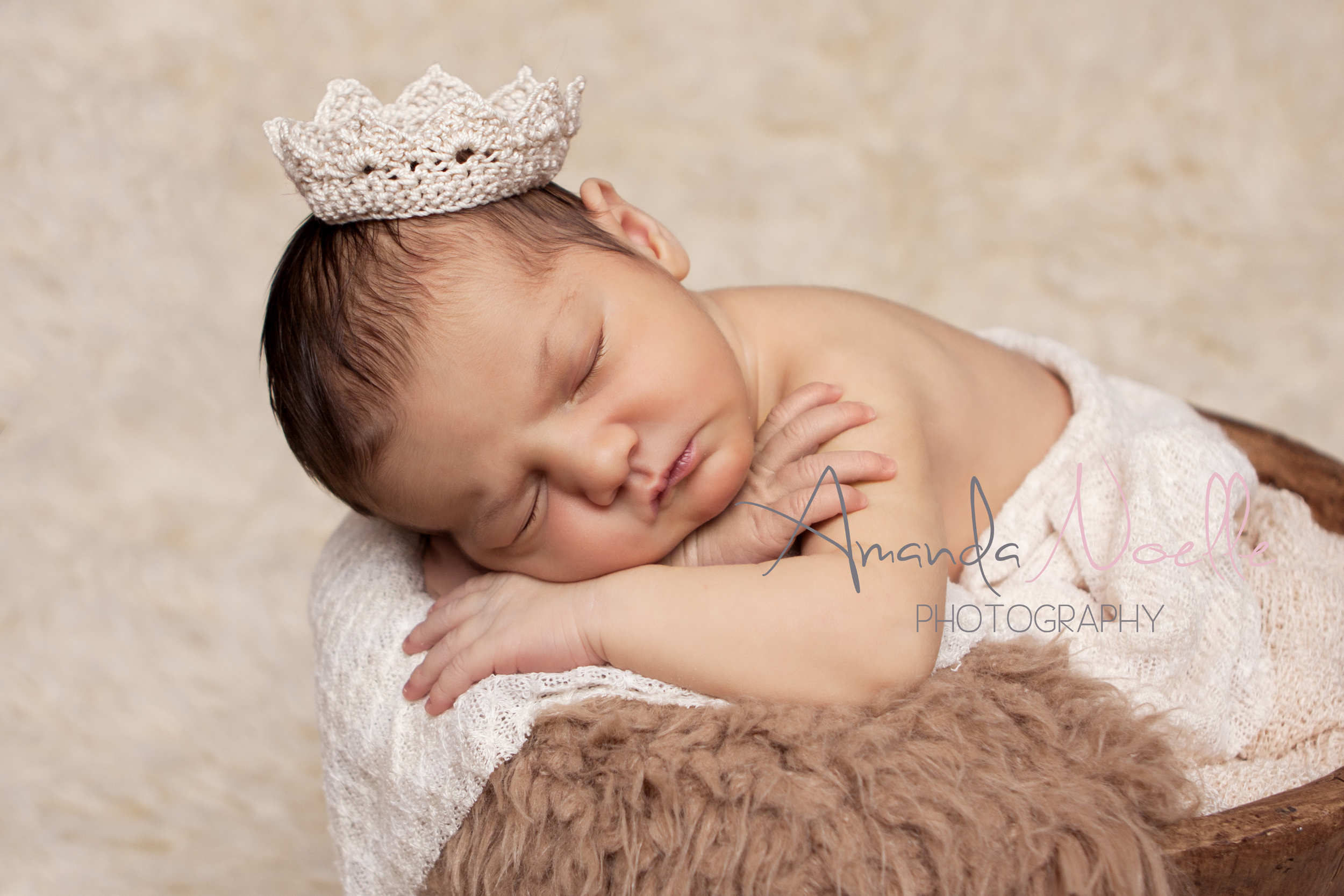 Newborn baby girl, in bucket, layering fabric and fur, tiny crochet princess crown tiara, brown creme, creme rug, sleeping prop pose by Westchester County, New York, Newborn Photographer, Amanda Noelle Photography.