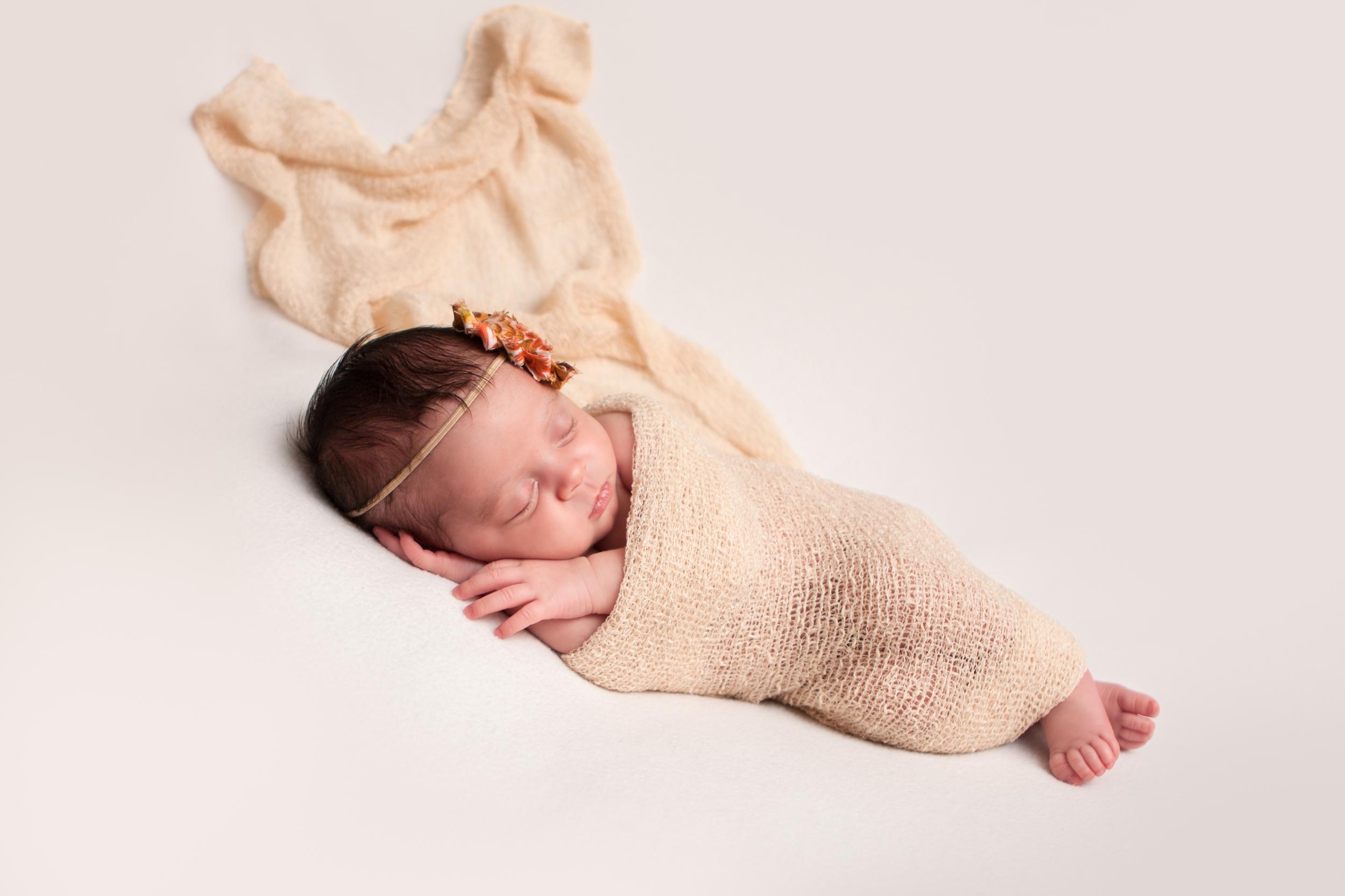 Newborn baby girl, shabby chic headband orange brown creme, creme white backdrop fabric blanket, creme tan stretch wrap, sleeping baby pose on beanbag, Westchester County, New Rochelle, White Plains, Pelham, New York Newborn Photographer, Amanda Noelle Photography