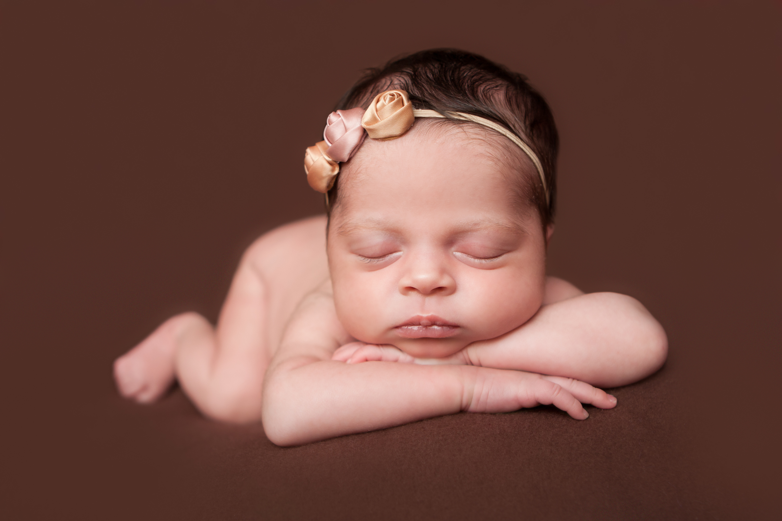 Newborn baby girl, shabby rosebud flower headband orange pink nude, brown backdrop fabric blanket, head chin on hands pose, sleeping baby pose on beanbag, Westchester County, New Rochelle, White Plains, Pelham, New York Newborn Photographer, Amanda Noelle Photography