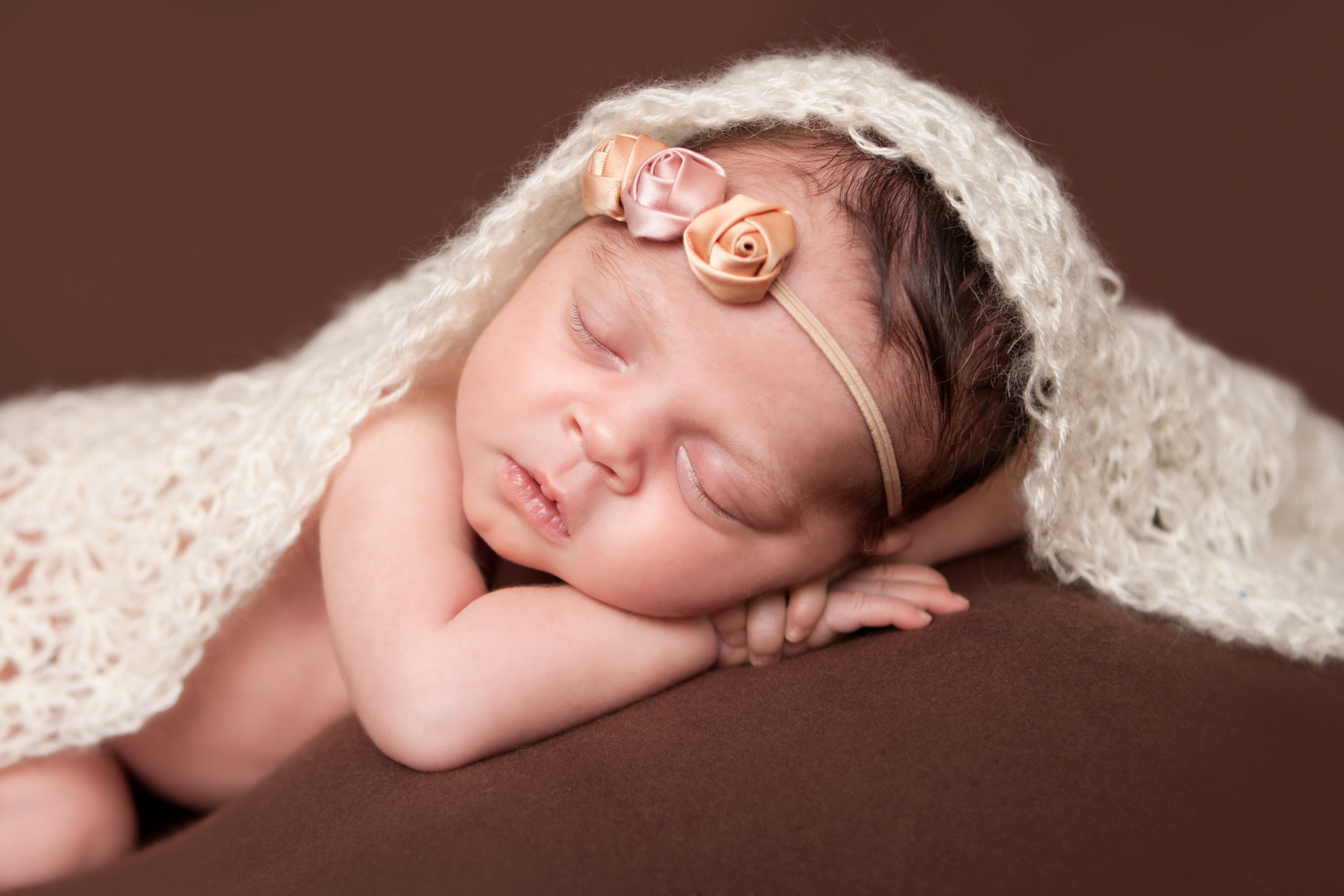 Newborn baby girl, shabby rosebud flower headband orange pink nude, brown backdrop fabric blanket, white creme crochet wrap, head on hands pose, sleeping baby pose on beanbag, Westchester County, New Rochelle, White Plains, Pelham, New York Newborn Photographer, Amanda Noelle Photography