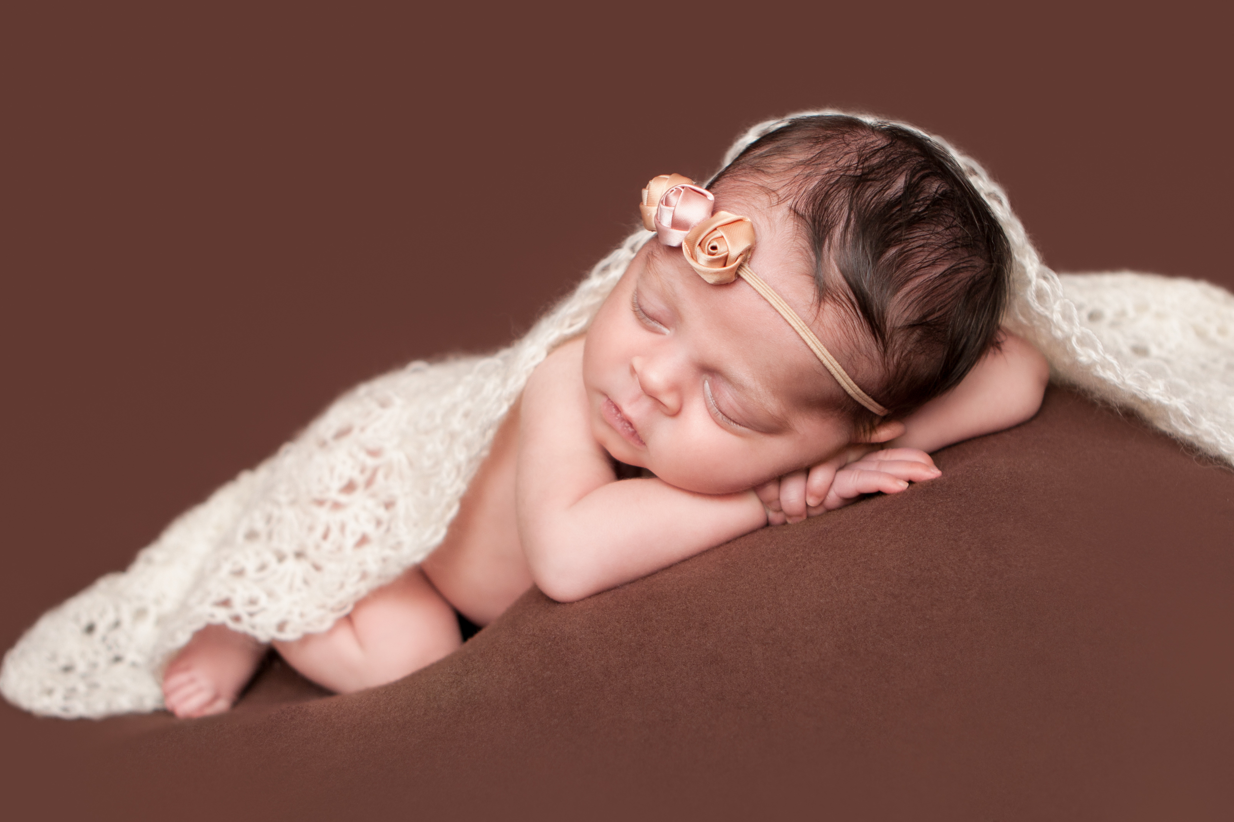 Newborn baby girl, shabby rosebud flower headband orange pink nude, brown backdrop fabric blanket, white creme crochet wrap, head on hands pose, sleeping baby pose on beanbag, Westchester County, New Rochelle, White Plains, Pelham, New York Newborn Photographer, Amanda Noelle Photography