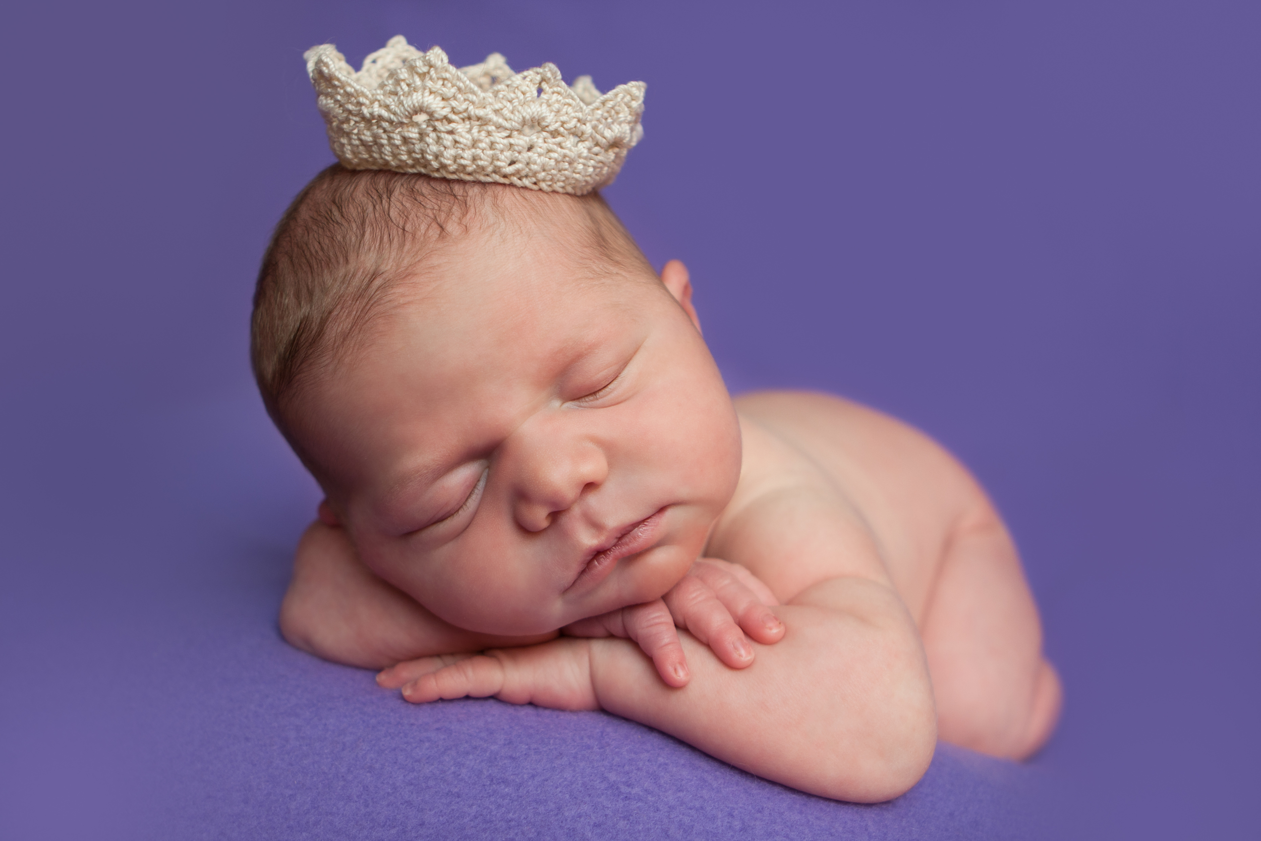 Newborn baby girl with crochet tiny crown, chin on wrists head on hands   bean bag pose on purple fabric backdrop, Westchester County, New York Newborn Photographer, Amanda Noelle Photography.