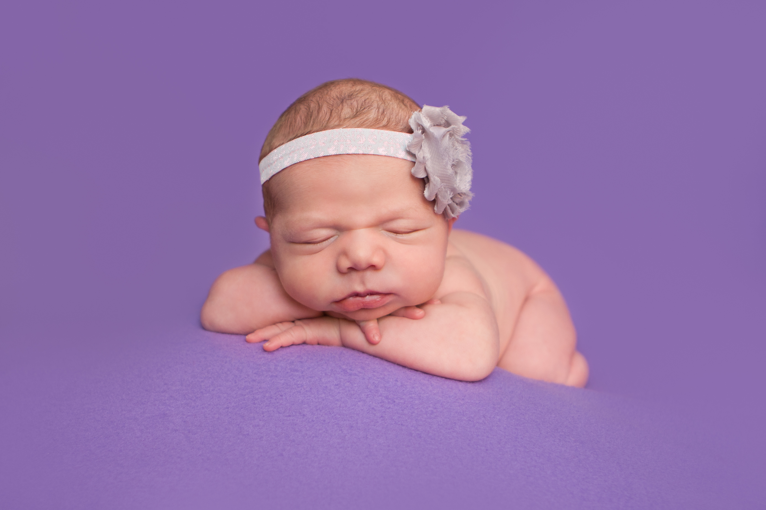 Newborn baby girl with shabby chic headband grey purple,   head on wrists chin on hands bean bag pose on purple fabric backdrop, Westchester County, New York Newborn Photographer, Amanda Noelle Photography.
