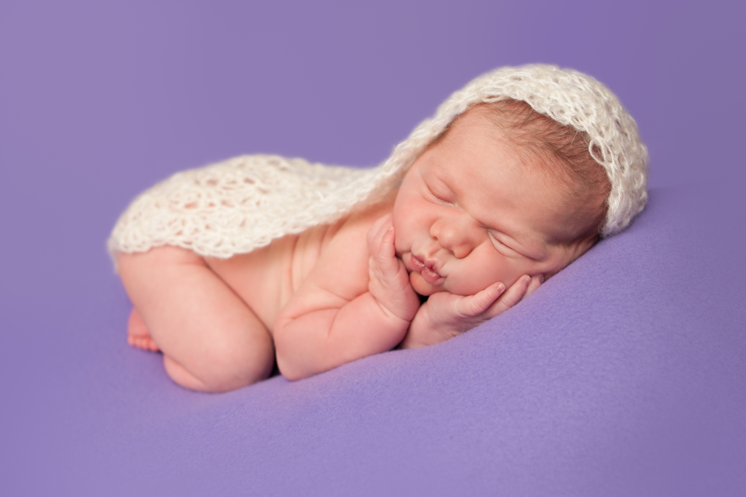 Newborn baby girl with lace crochet wrap, hands on cheeks   bean bag pose on purple fabric backdrop, Westchester County, New York Newborn Photographer, Amanda Noelle Photography.