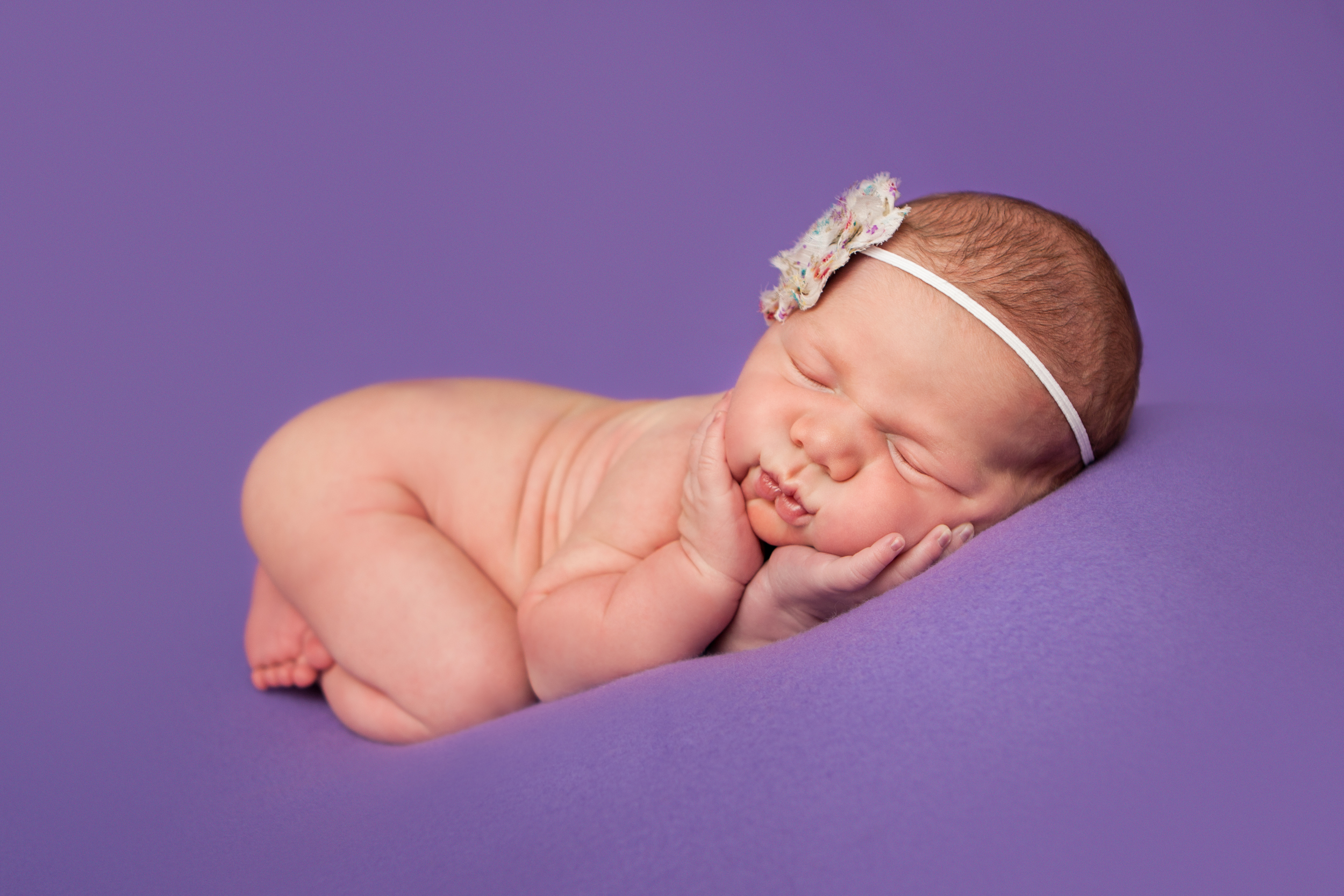 Newborn baby girl with shabby chic white flower headband, hands on cheeks   bean bag pose on purple fabric backdrop, Westchester County, New York Newborn Photographer, Amanda Noelle Photography.