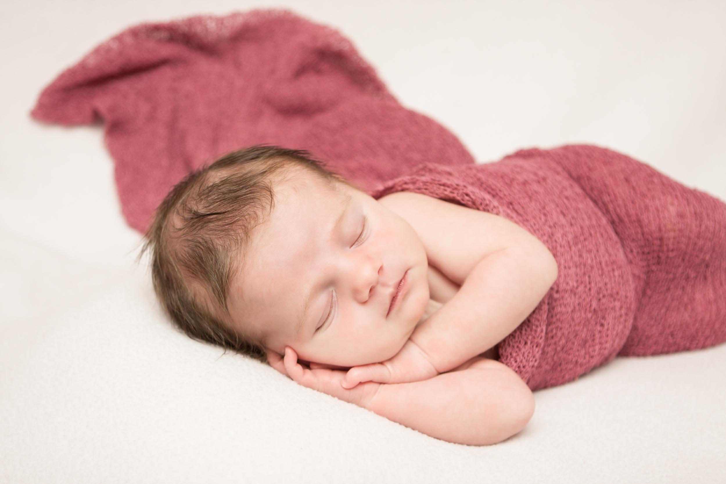 Newborn baby girl, pink berry maroon stretch wrap, on white fabric blanket backdrop, beanbag pose, Westchester County, New York Newborn Photographer, Amanda Noelle Photography.