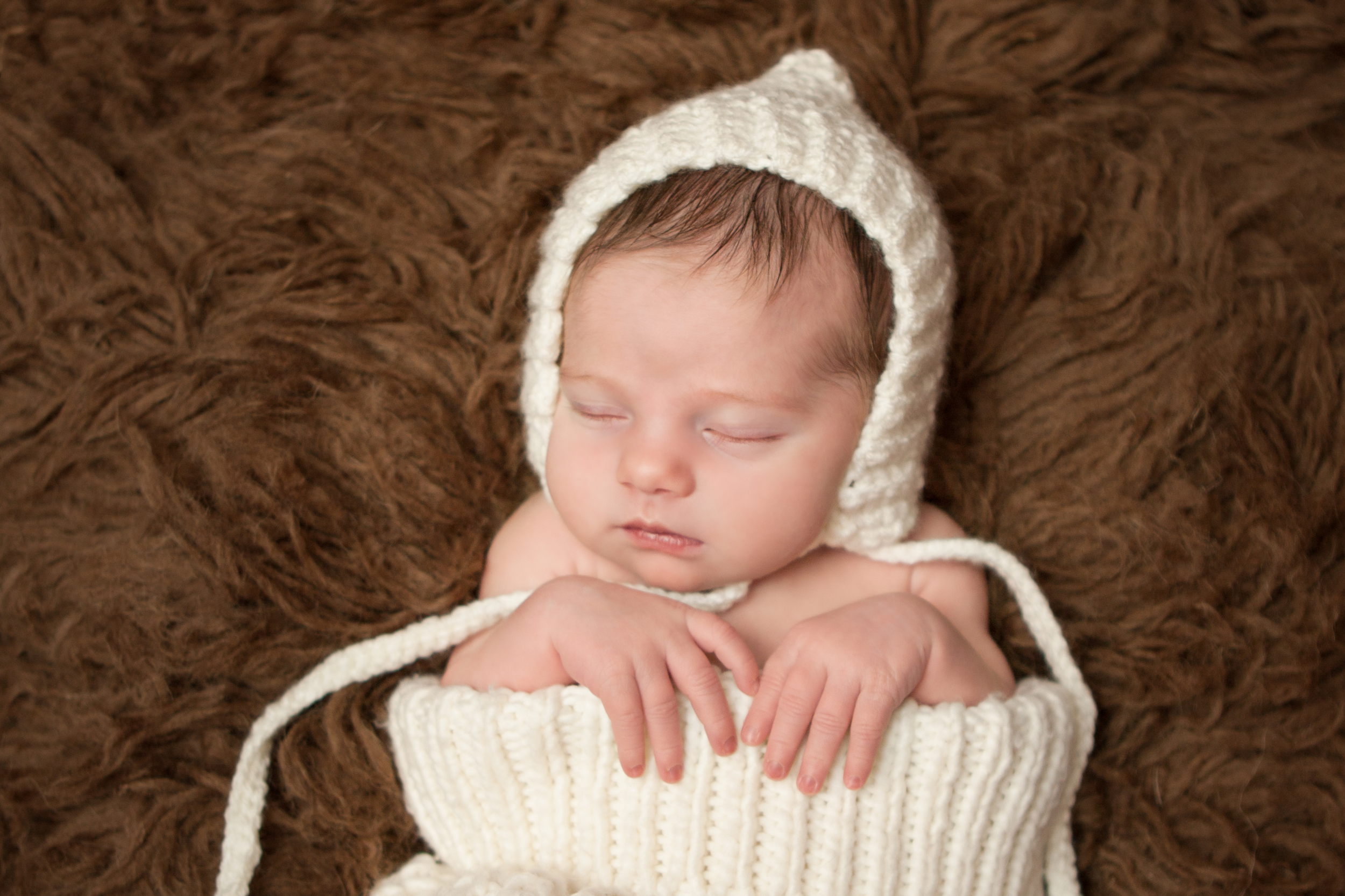 Newborn baby girl  , creme white crochet bonnet in, in creme white crochet knit wrap sack on brown flokati rug, Westchester County, New York Newborn Photographer, Amanda Noelle Photography.