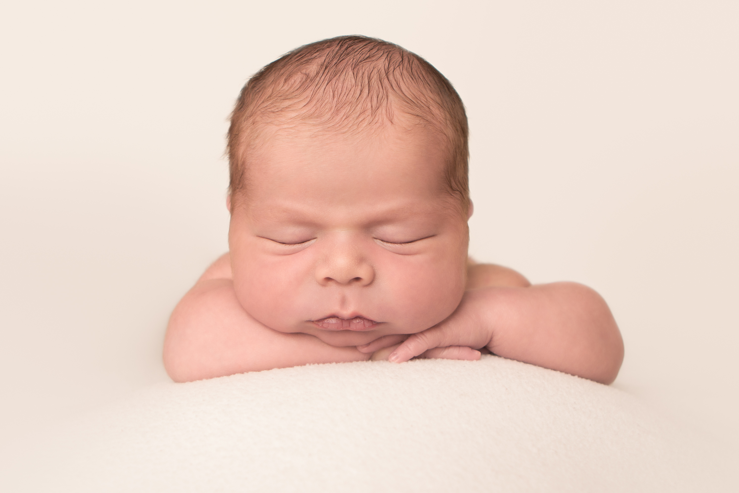 Newborn baby boy chubby, on cream creme white fabric blanket backdrop, head on hands wrists bean bag pose,  Westchester County, New York newborn photographer, Amanda Noelle Photography.