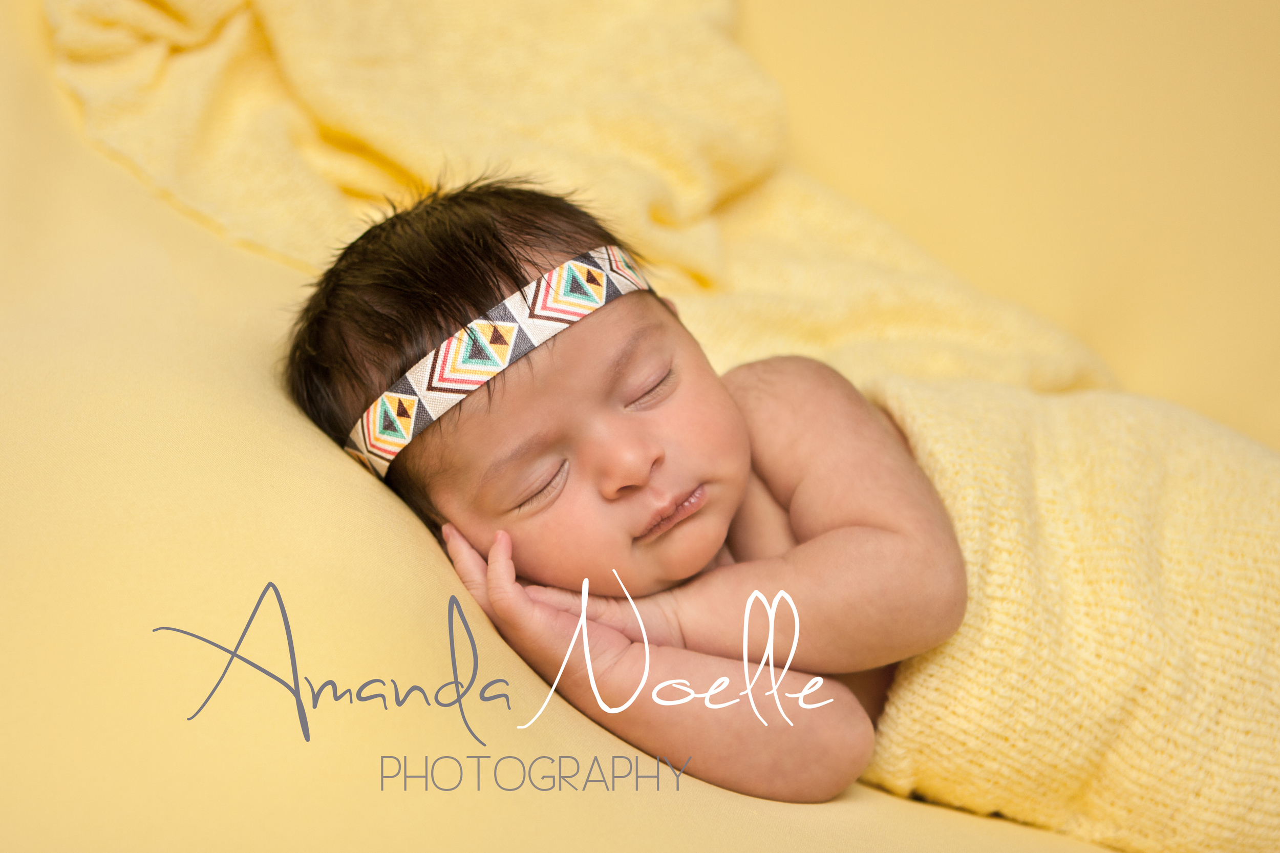 Newborn baby girl sleeping with bohemian aztec headband wrapped in yellow stretch knit wrap on yellow fabric backdrop, beanbag pose, Westchester, County New York Newborn Photographer, Amanda Noelle Photography.